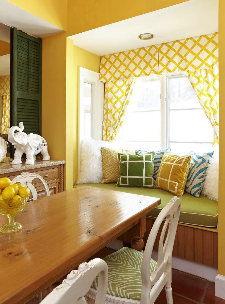 Уютная ниша в столовой с желтыми стенами и шторами