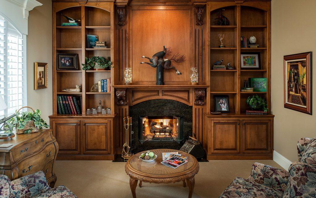 Круглый журнальный стол из дерева и плетеного ротанга в гостиной в стиле кантри