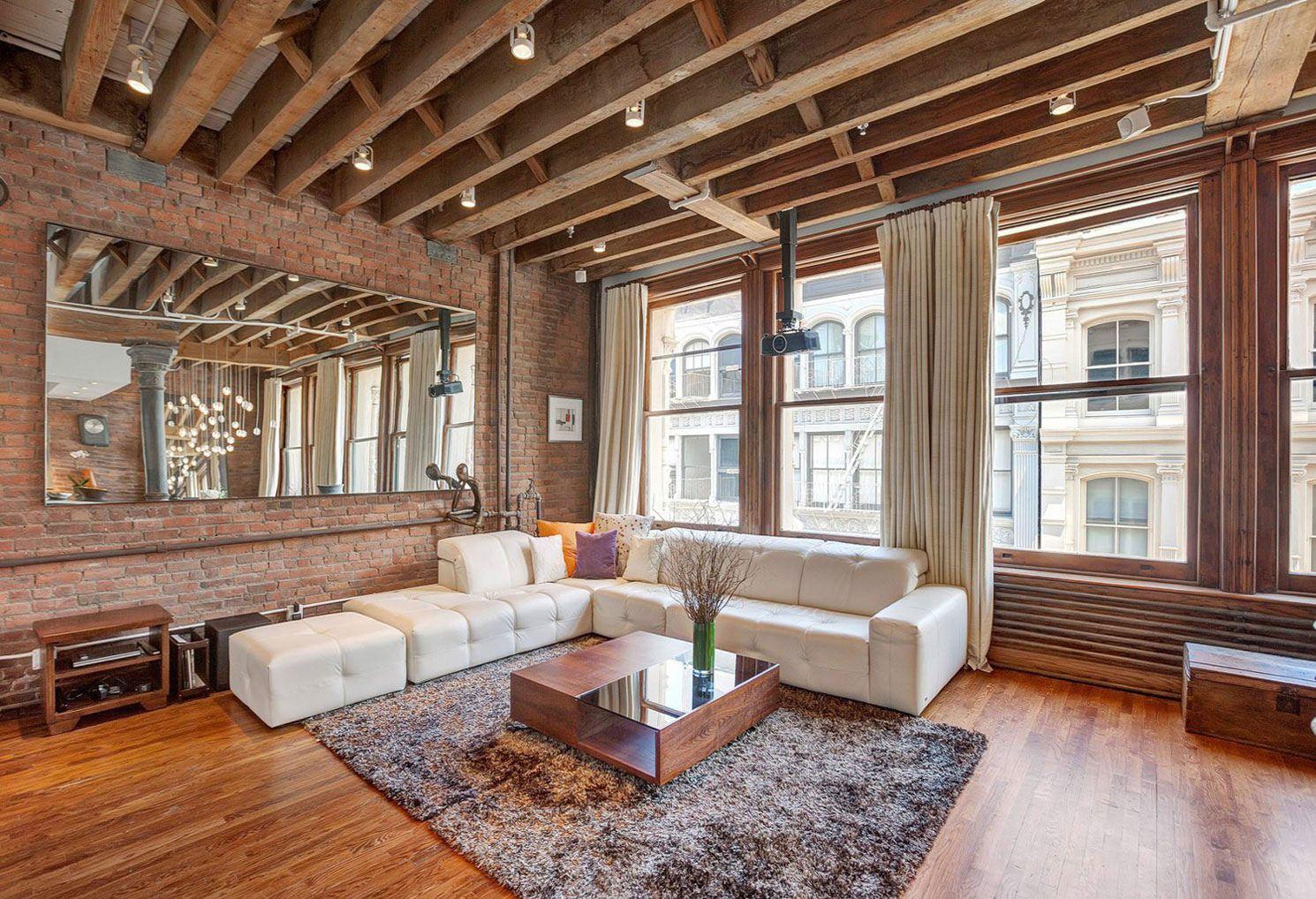 Деревянные балки на потолке в гостиной с кирпичными стенами