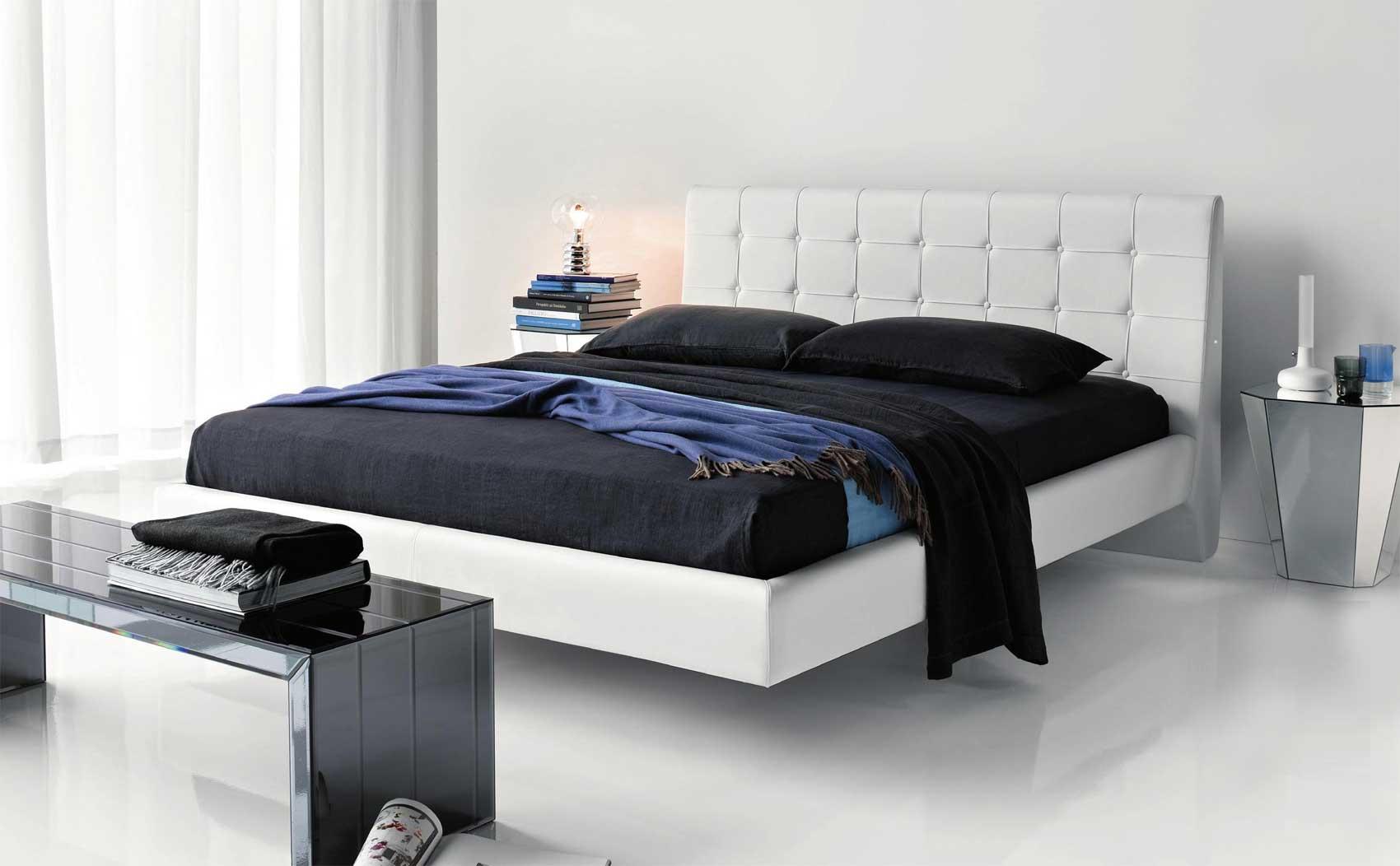 Белая кровать с черным постельным бельем в спальне