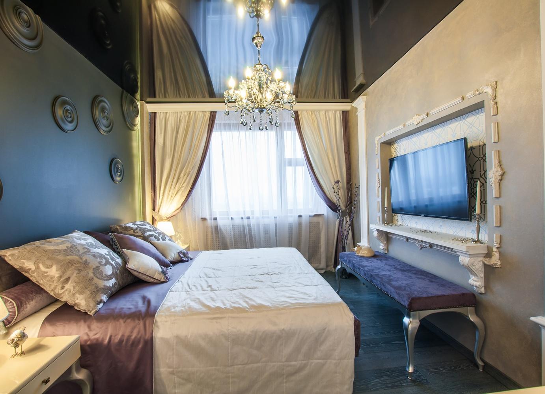 Черный глянцевый потолок в светлой спальне