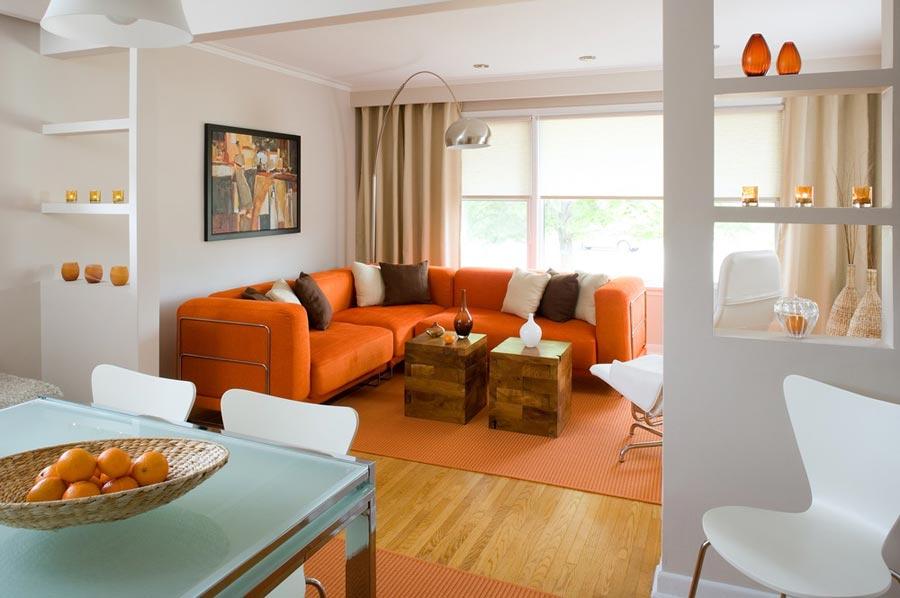 Оранжевый угловой диван и ковер в гостиной