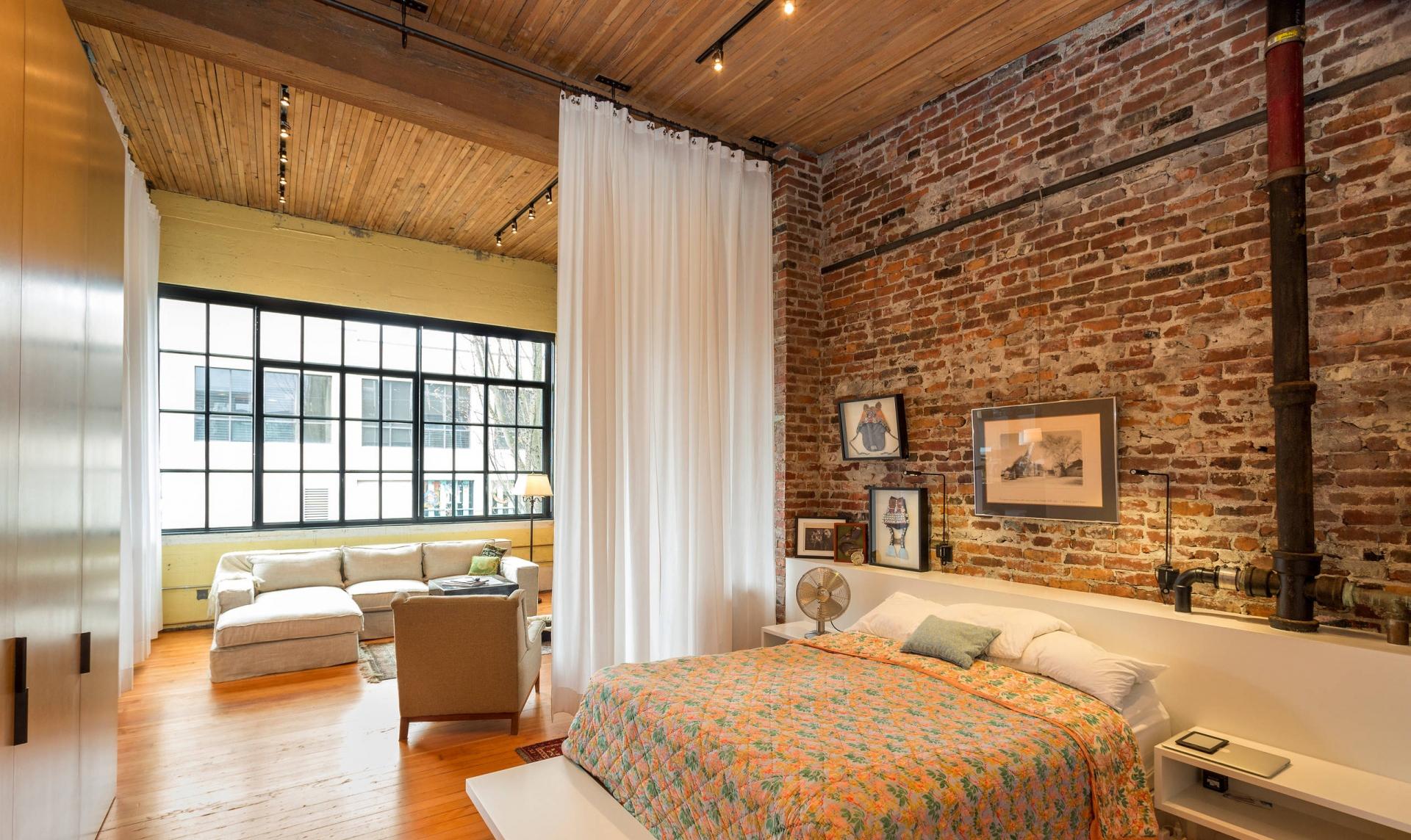 Спальня в индустриальном стиле с кирпичной стеной