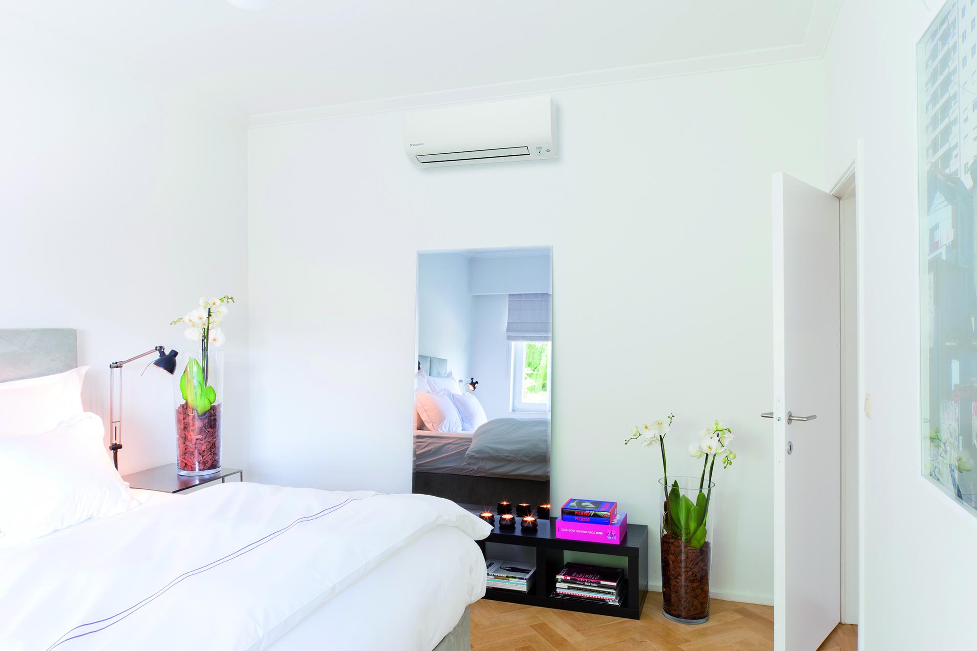 Белый кондиционер в спальне с белыми стенами