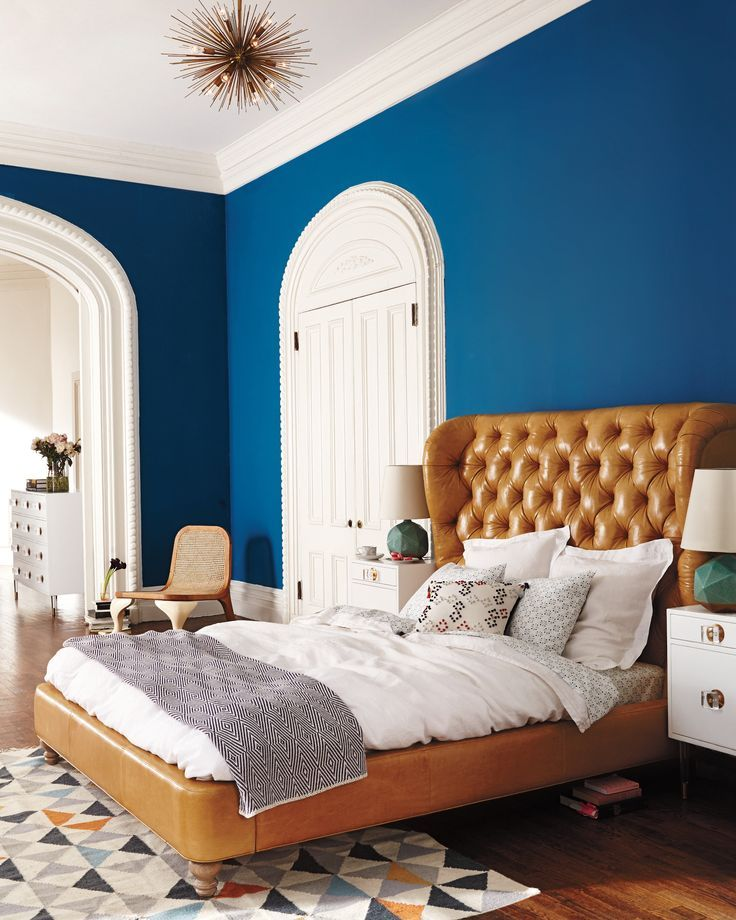 Коричневая кожаная кровать в бело-синей спальне