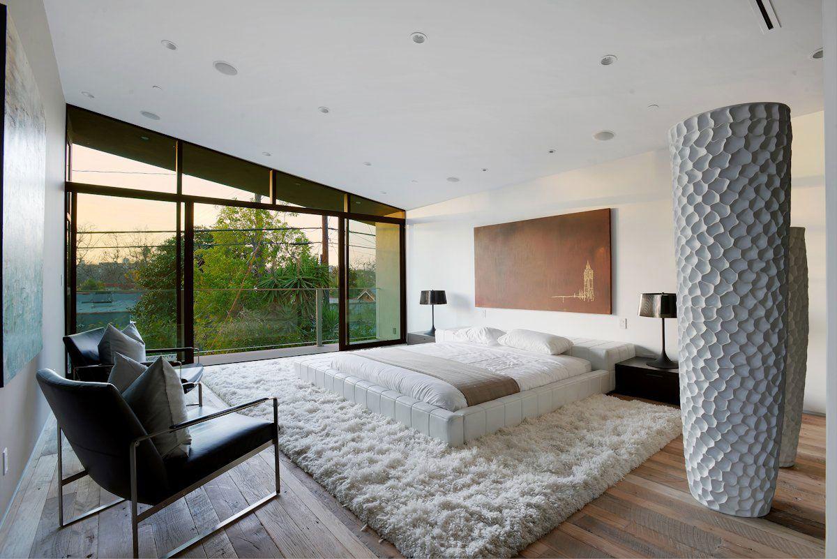 Низкая белая кожаная кровать в спальне в стиле минимализм