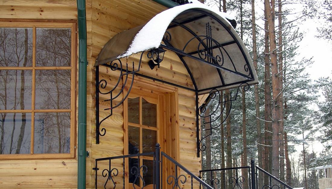 Арочный козырек загородного дома из кованого металла и поликарбоната