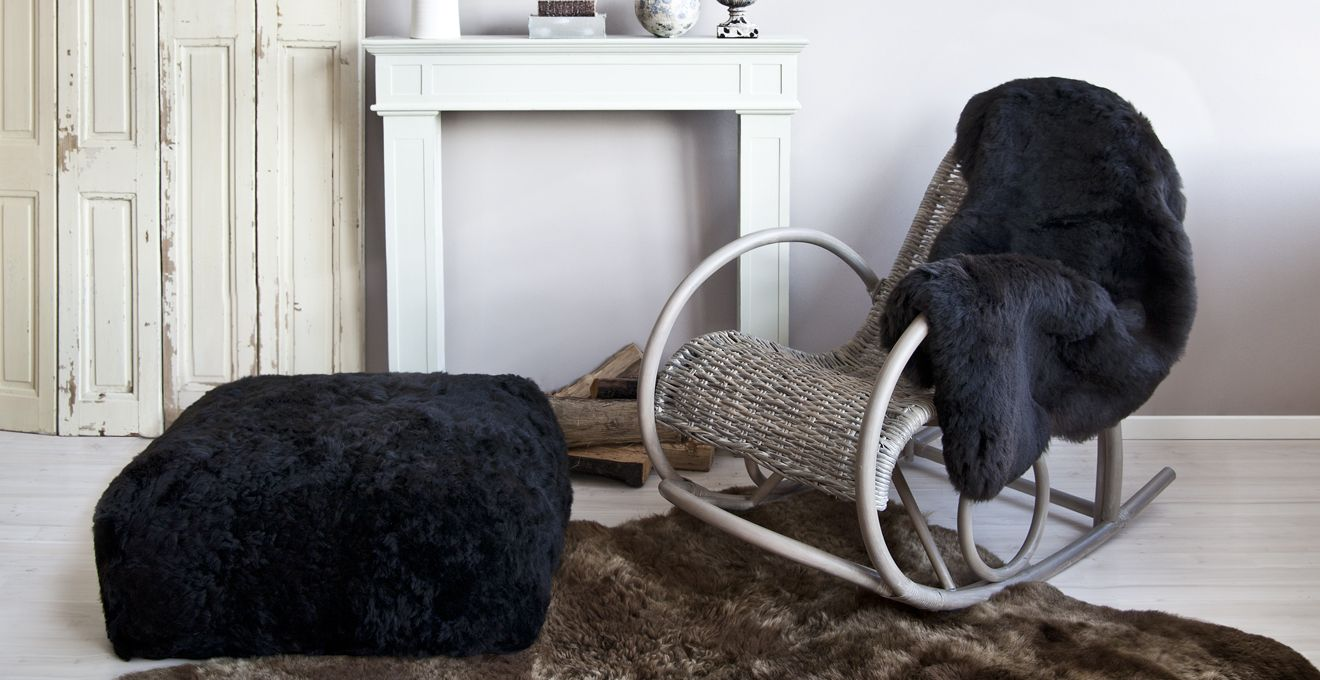 Серое плетеное кресло качалка в гостиной