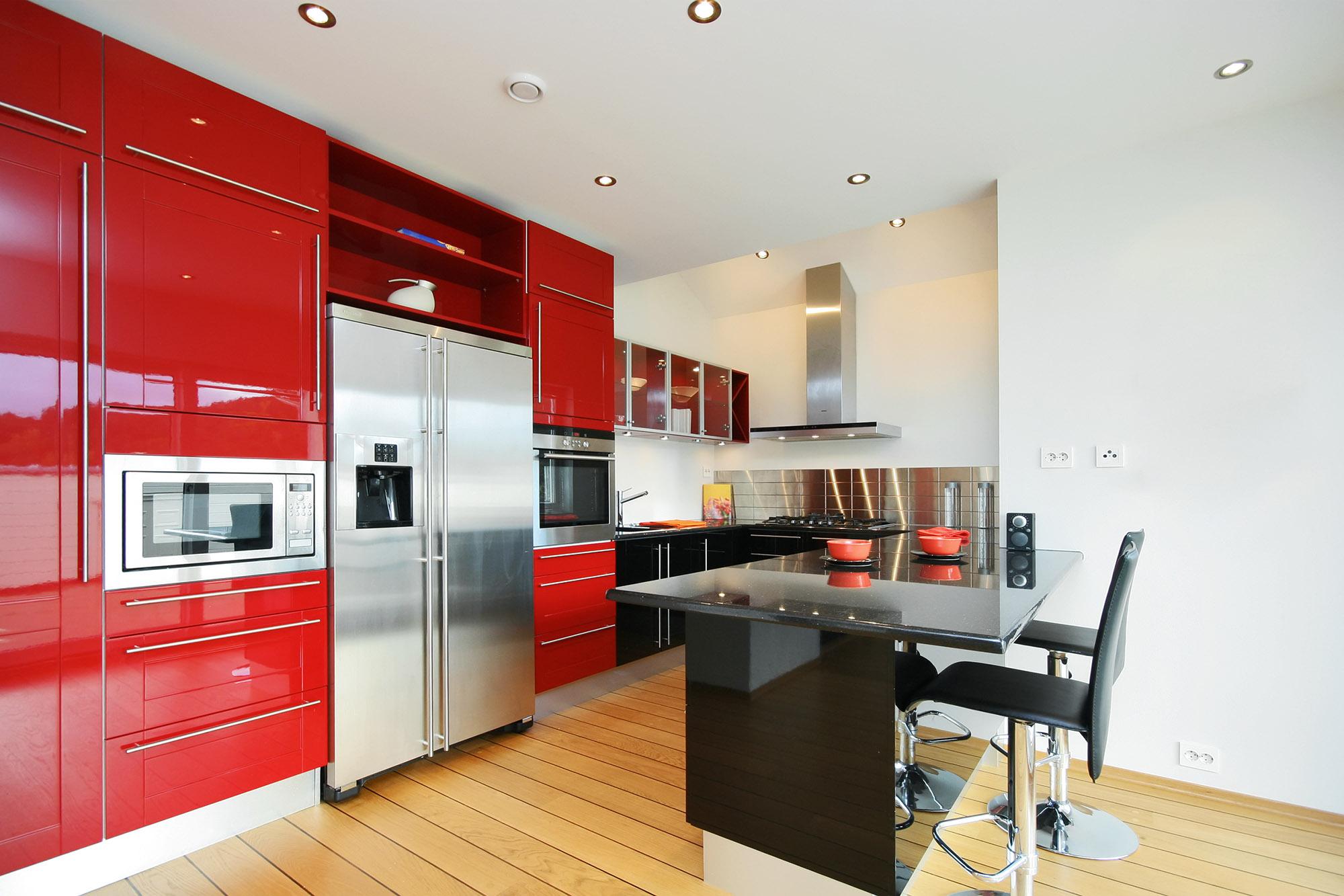 Красный кухонный гарнитур с черной и металлической мебелью на кухне