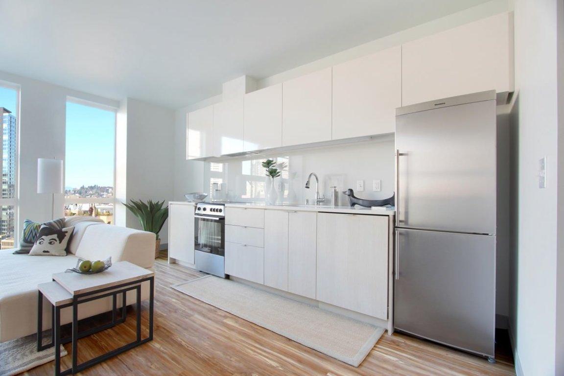 Коричневый пол в белой кухне-гостиной