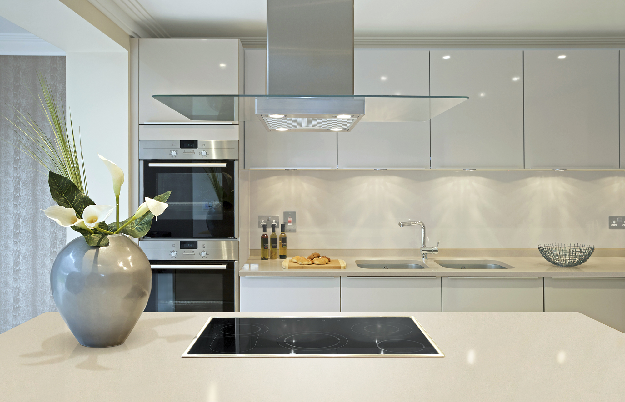 Белая кухня в стиле модерн с обильным освещением