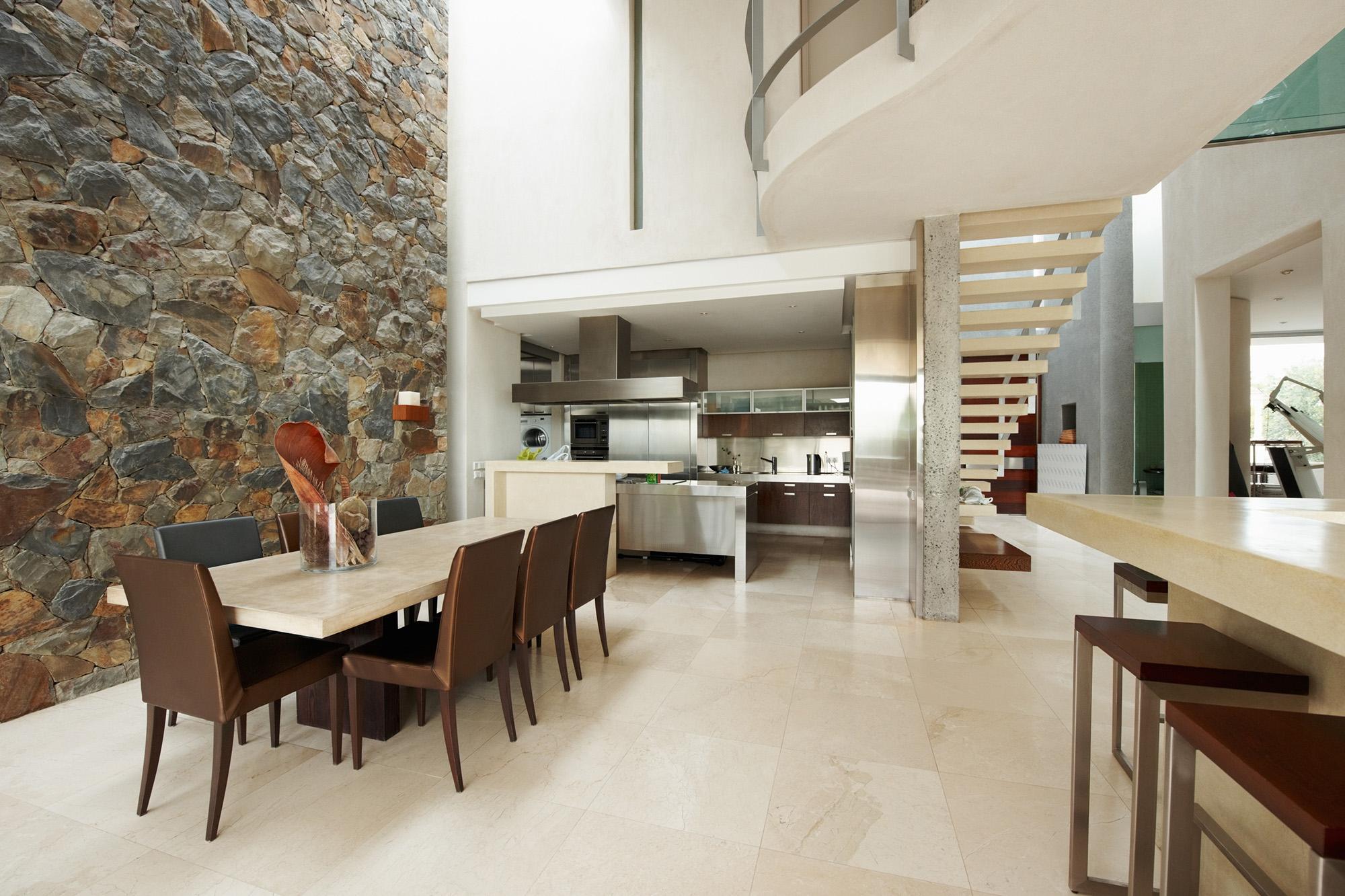 Крупный натуральный камень в отделке стены на кухне