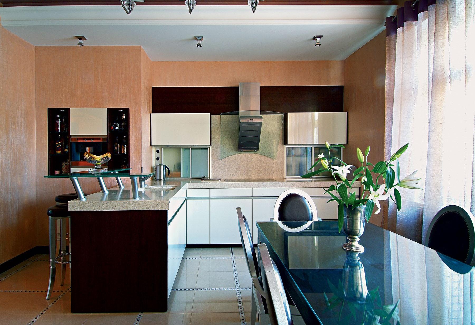 Персиковые стены в интерьере кухни с барной стойкой и обеденным столом
