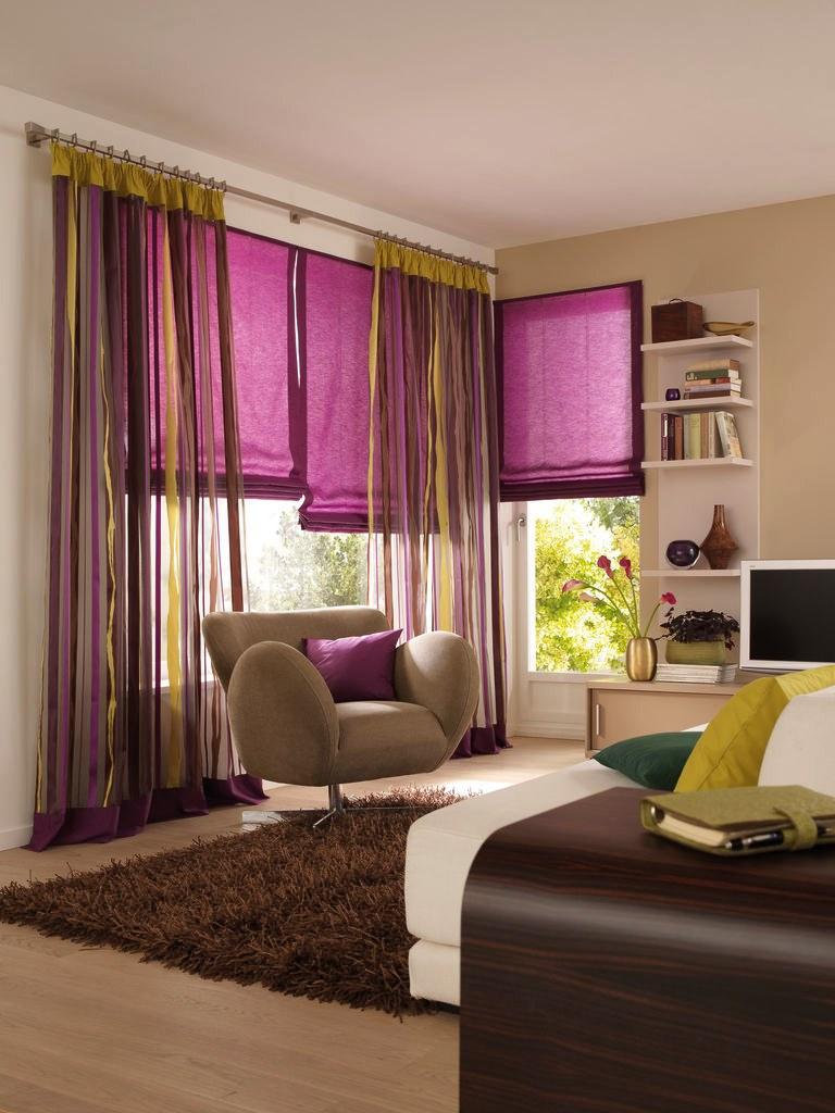 Комбинирование розовых римских штор и разноцветных обычных в интерьере гостиной
