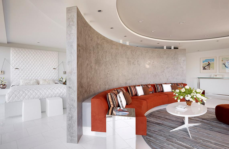 Полукруглая стена, отделанная серой штукатуркой