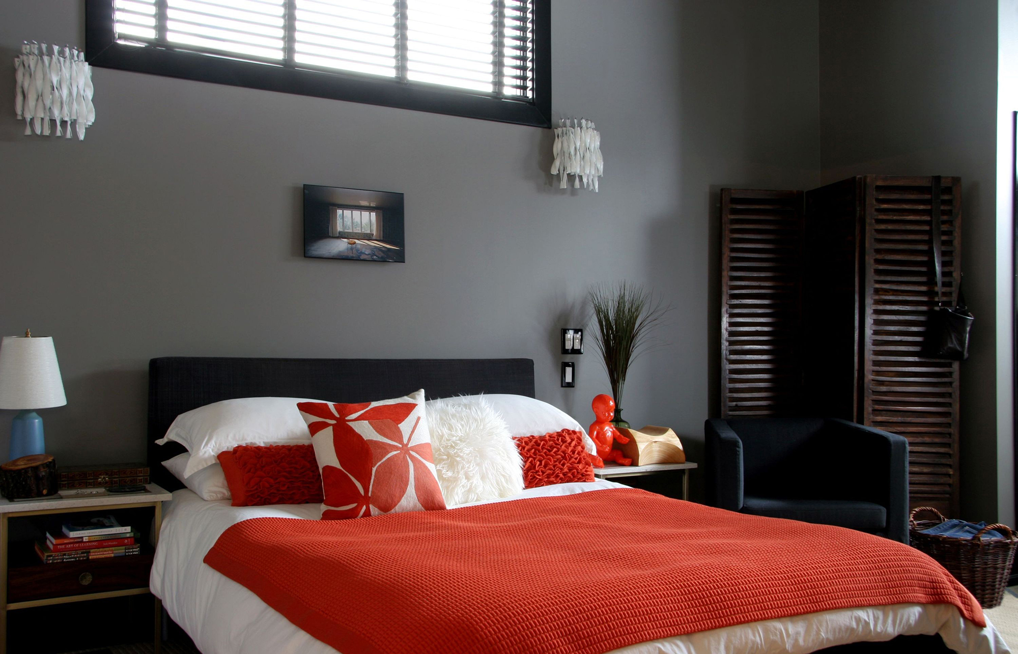 Красные акценты в спальне с настенными светильниками