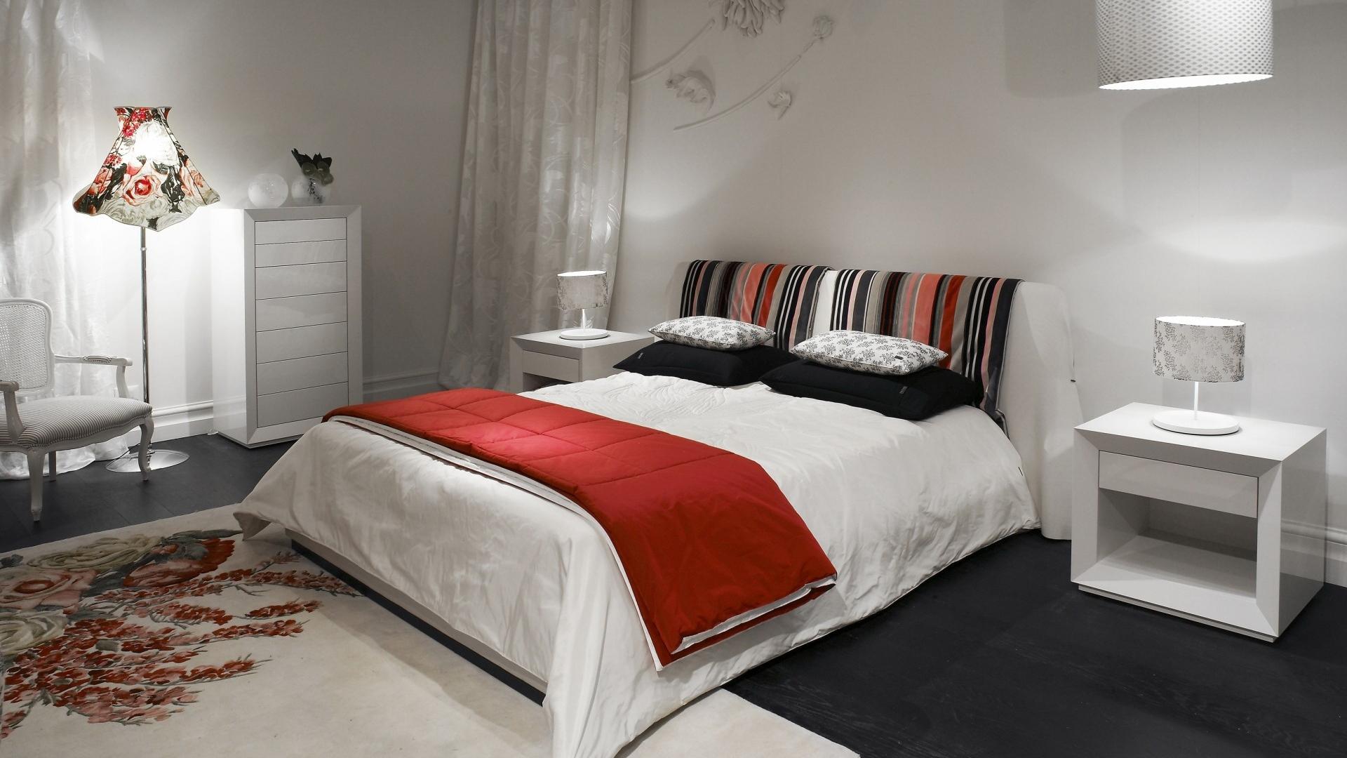 Обилие разных источников света в белой спальне с красными акцентами