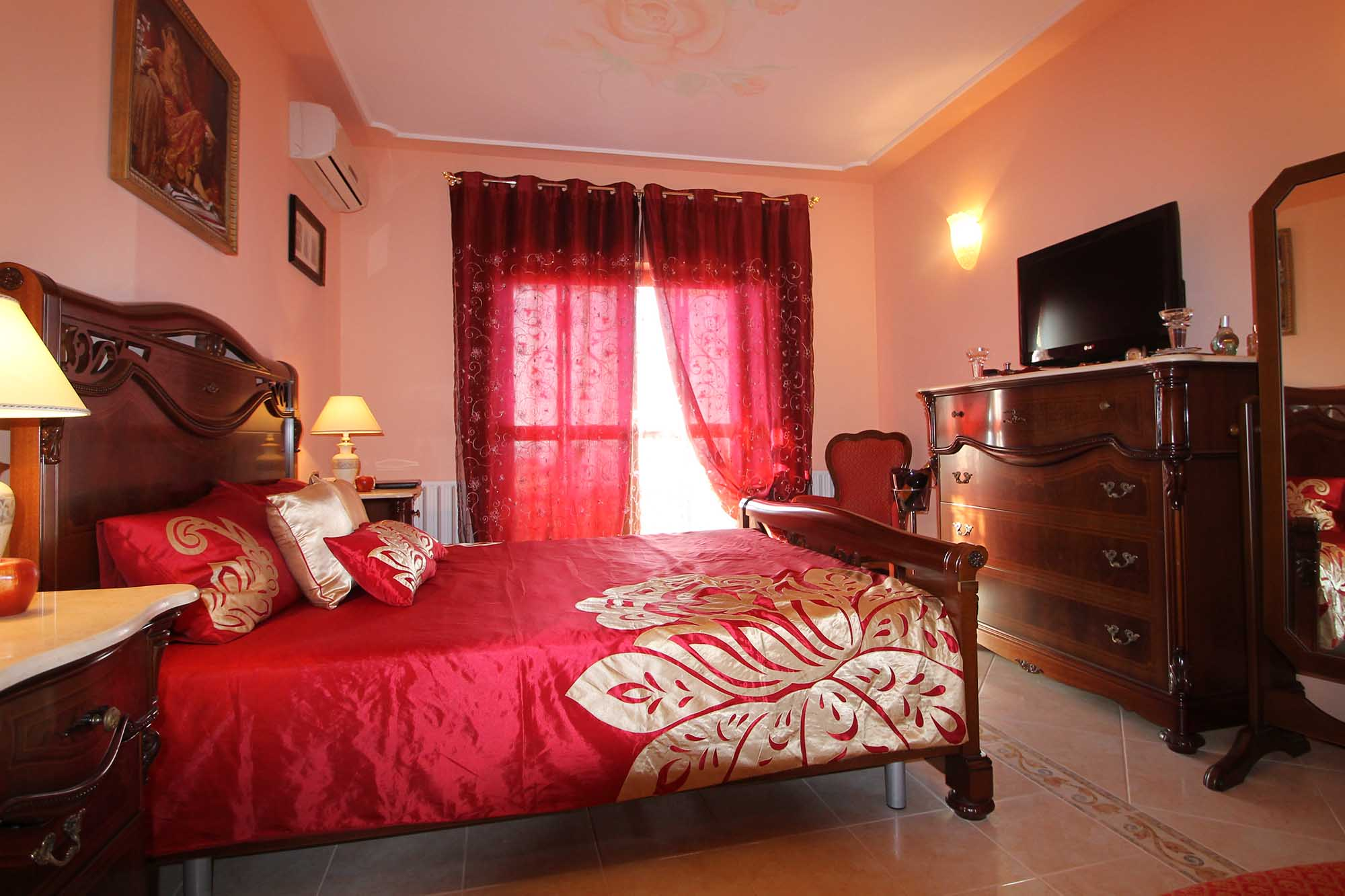 Красно-золотистые шторы и постельное белье в спальне