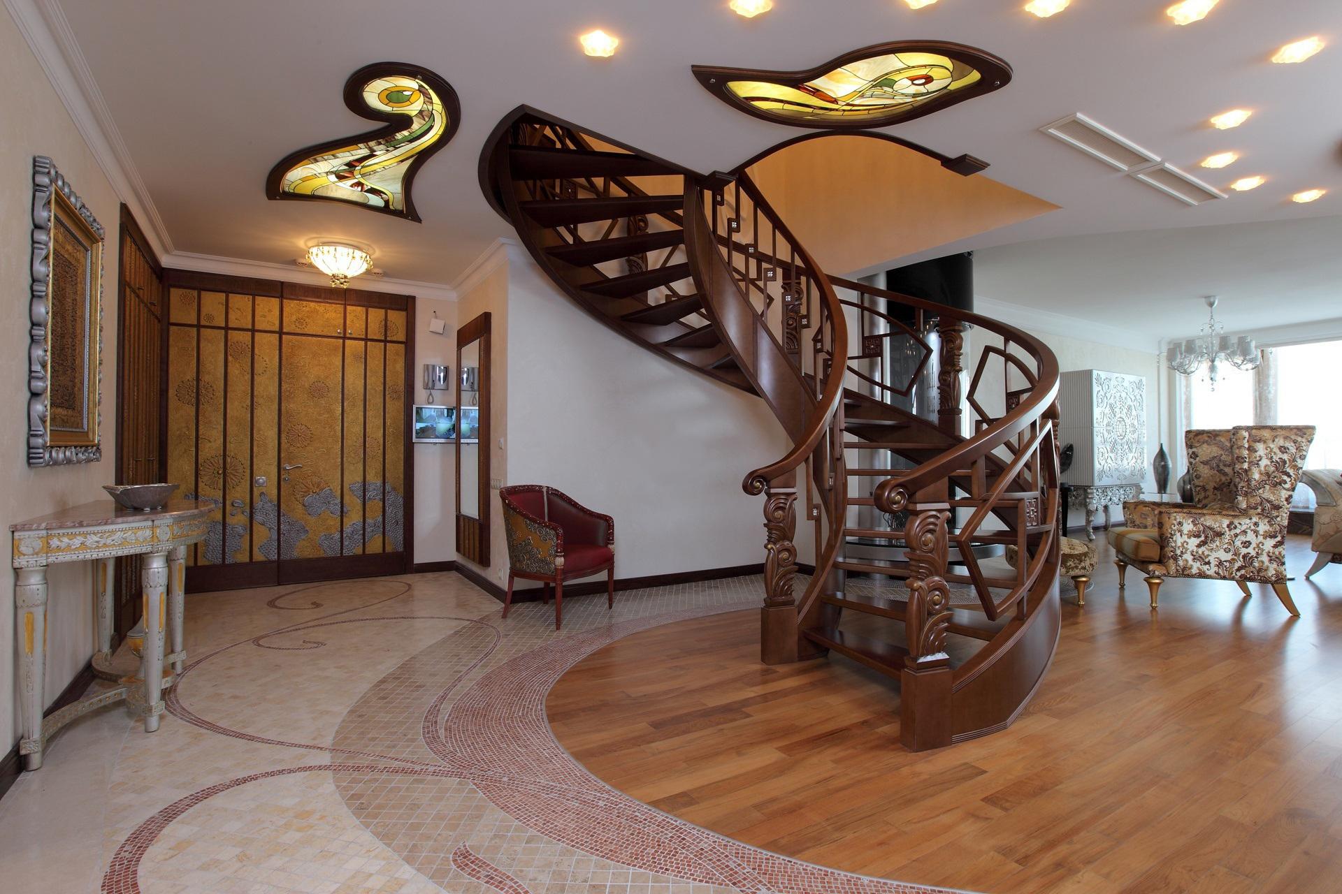 Бежевые стены и резная лестница в интерьере в стиле модерн