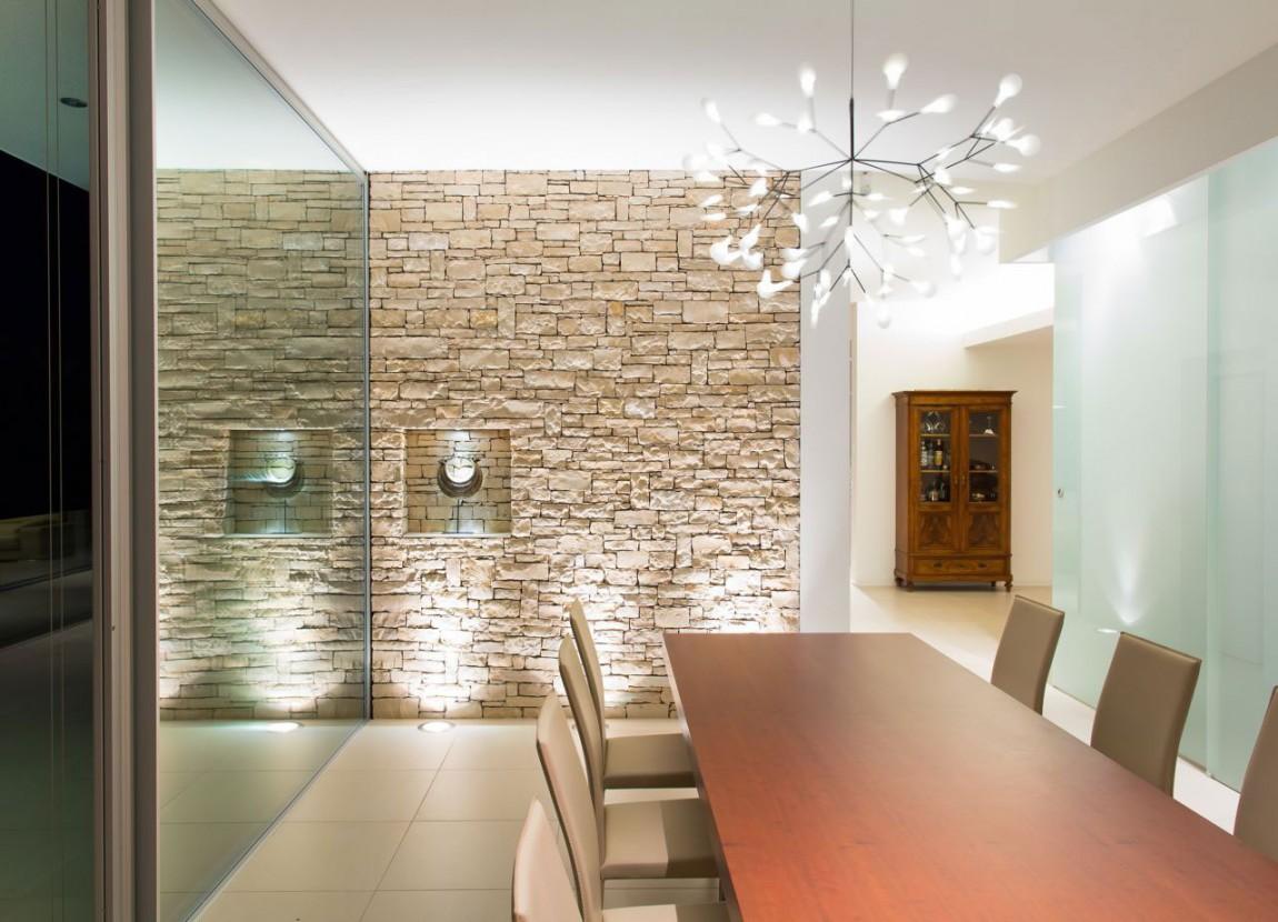 Отделка стен декоративным камнем с точечными светильниками