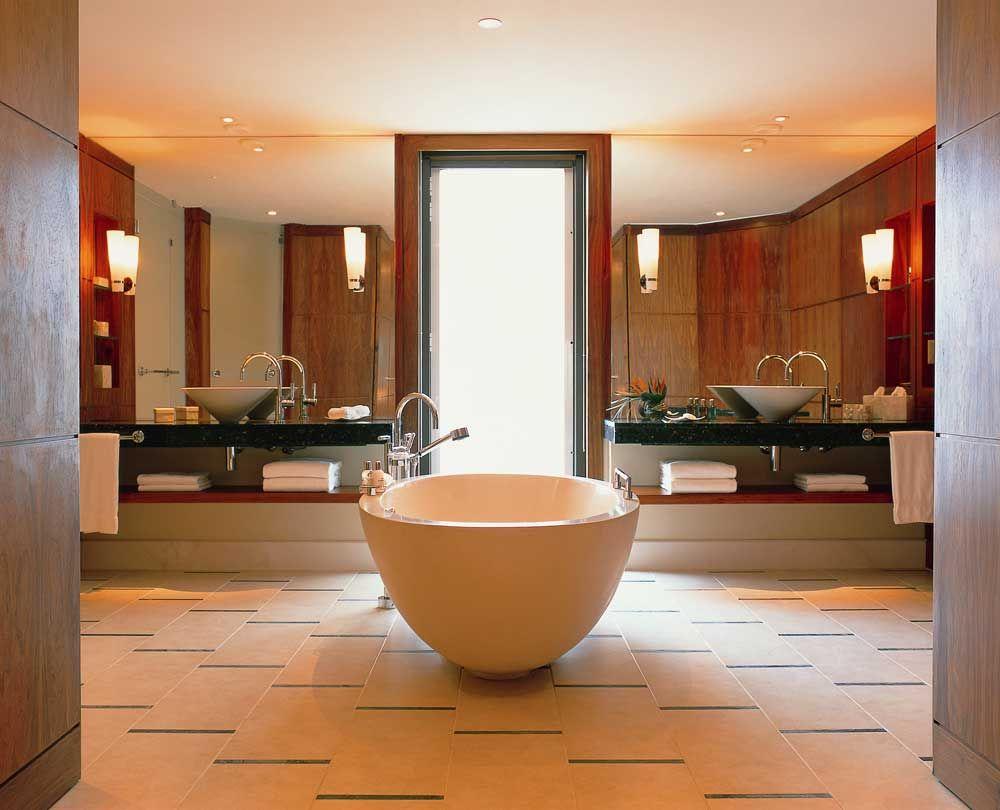 Просторная ванная комната с настенными лампами и большими зеркалами
