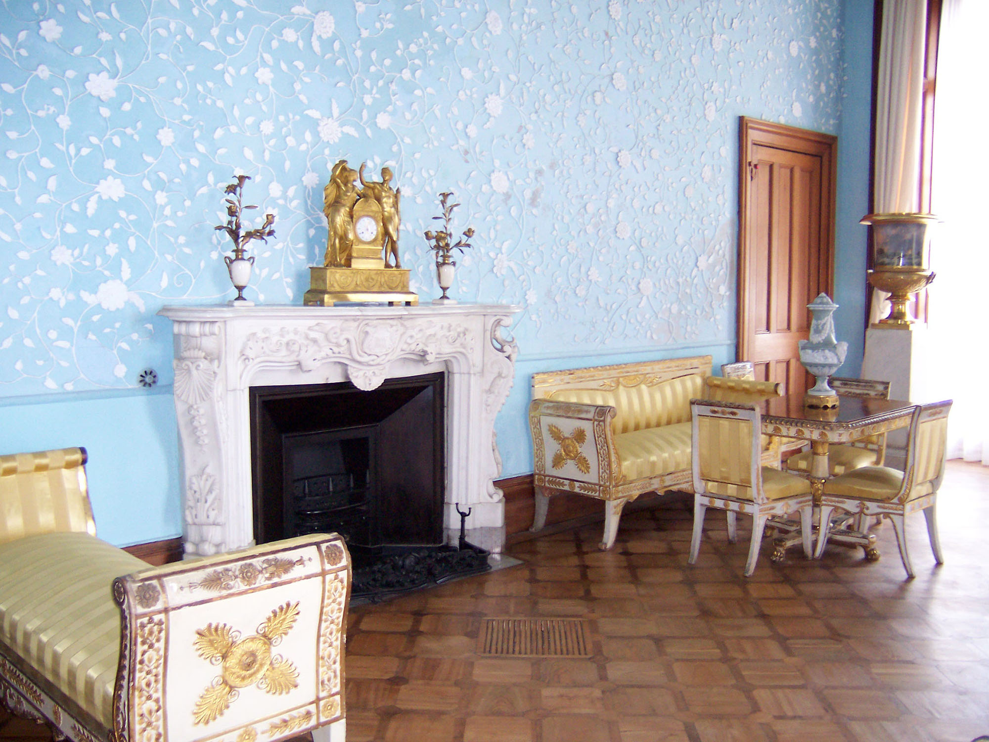 Голубой, золотой, белый и коричневый цвета в интерьере гостиной