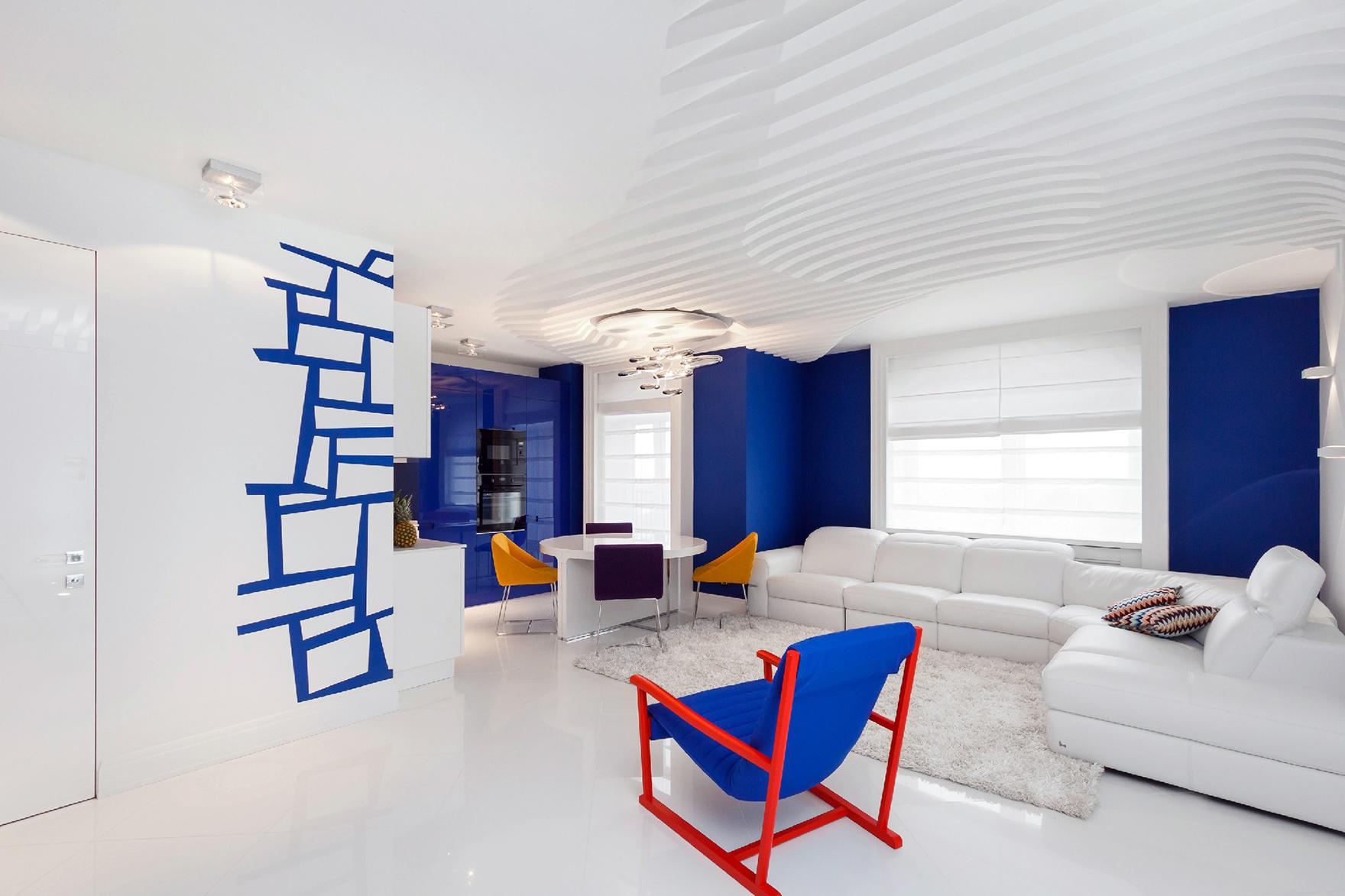 Синий, белый, красный и желтый цвета в интерьере гостиной-кухни