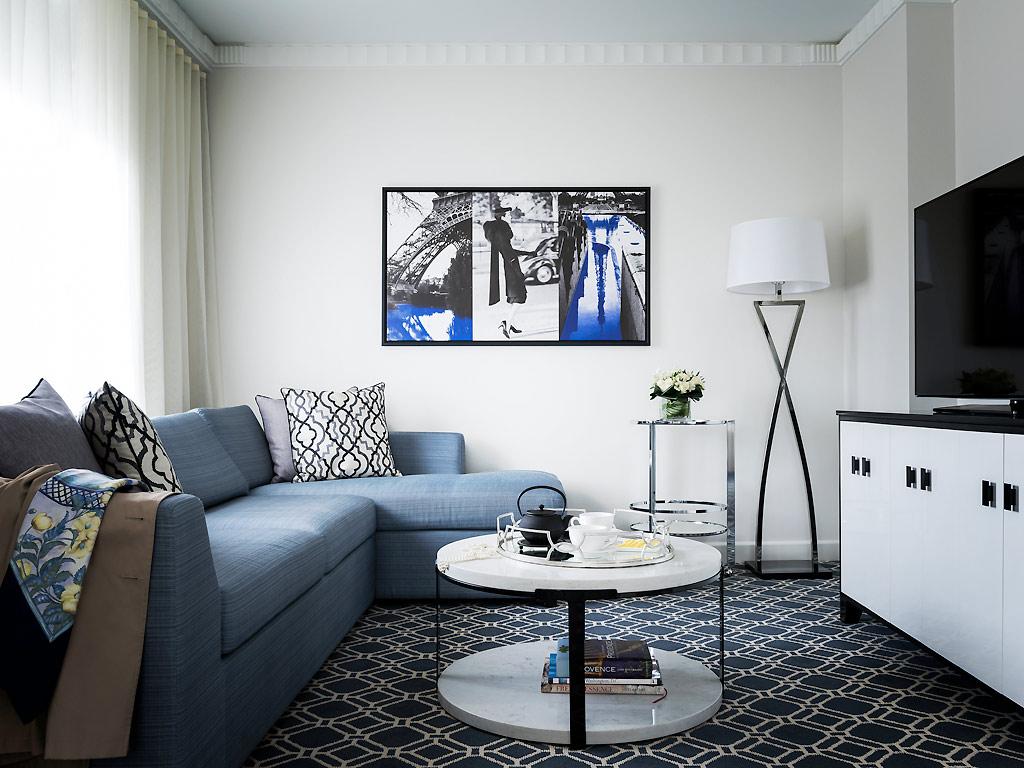 Синий угловой диван в черно-белой гостиной