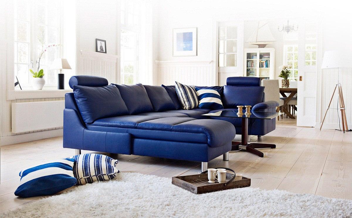 Белые стены в гостиной с синим диваном