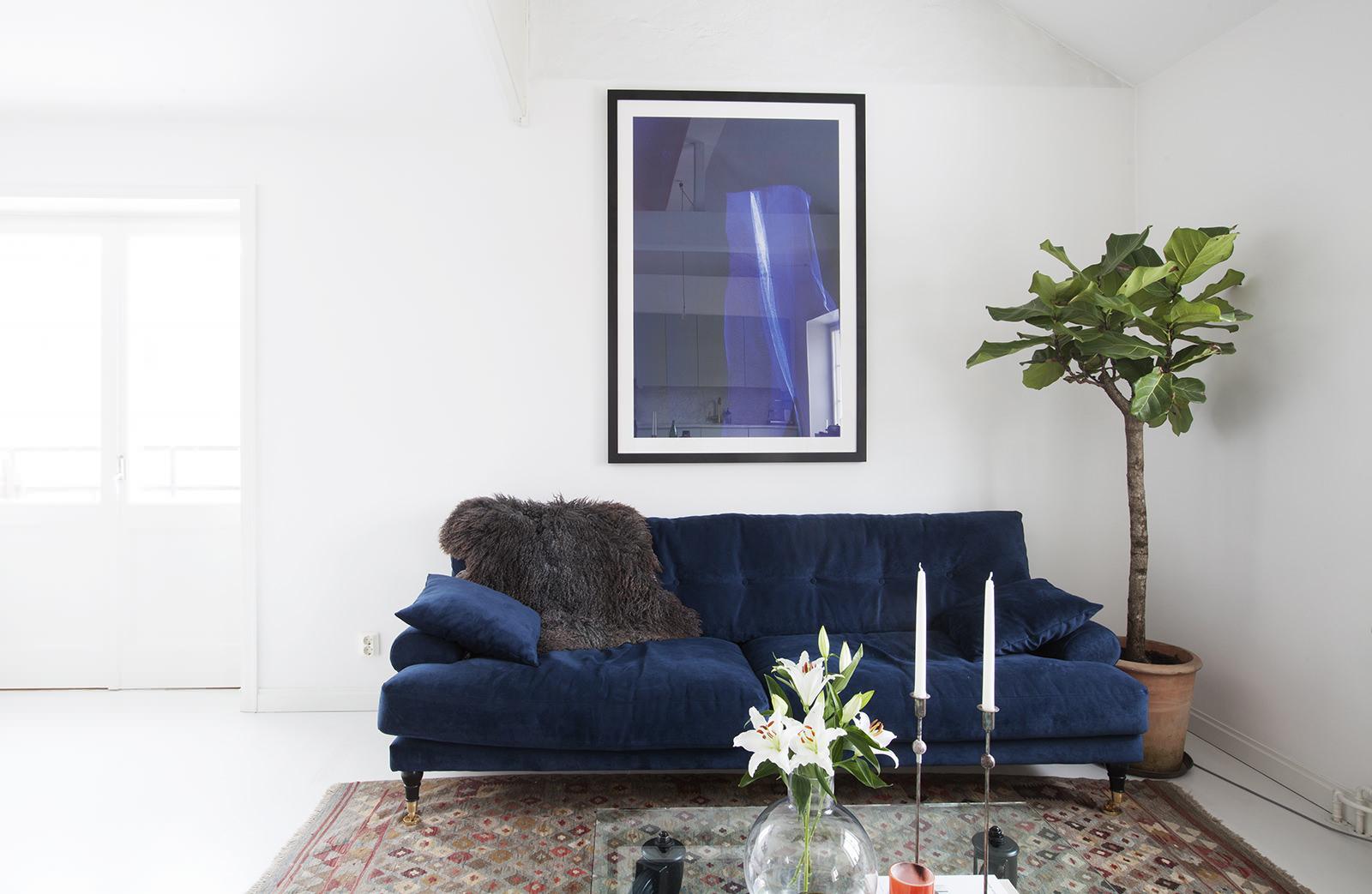 Синий диван и картина в белой гостиной