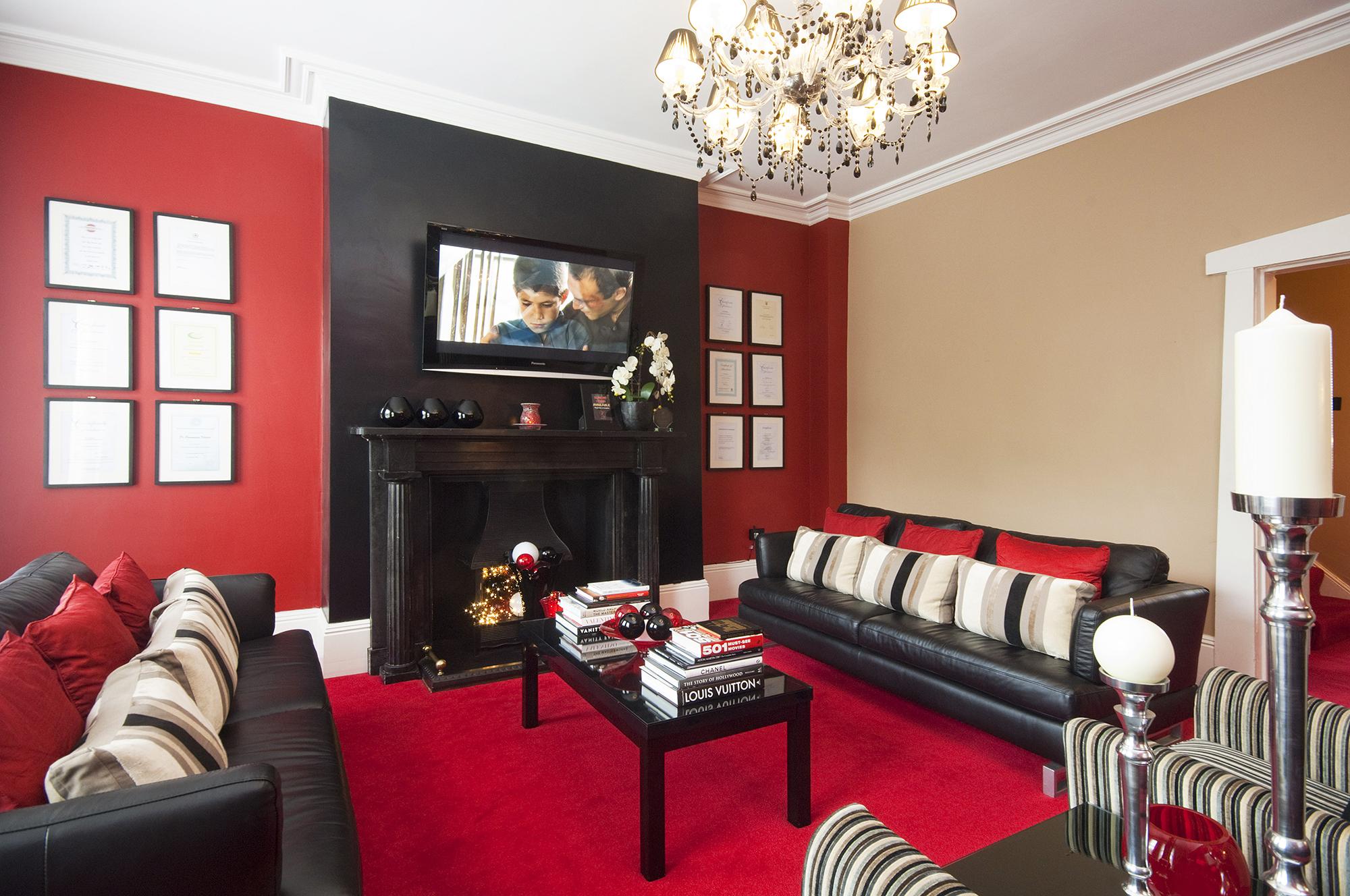 Красный, бежевый и белый цвета в интерьере гостиной с камином