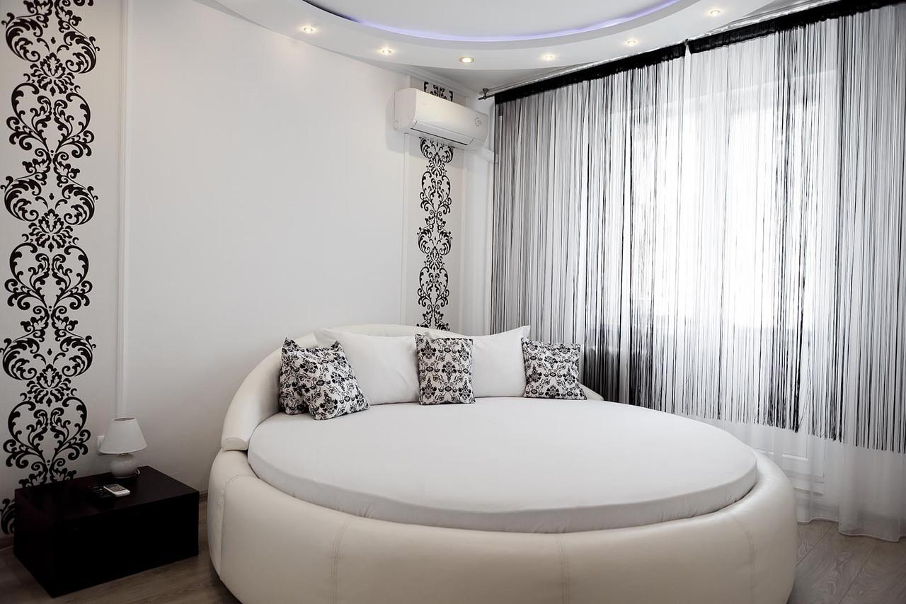 Круглая белая кожаная кровать в спальне