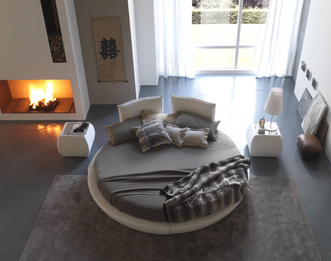 Серо-белая круглая кровать в спальне с камином