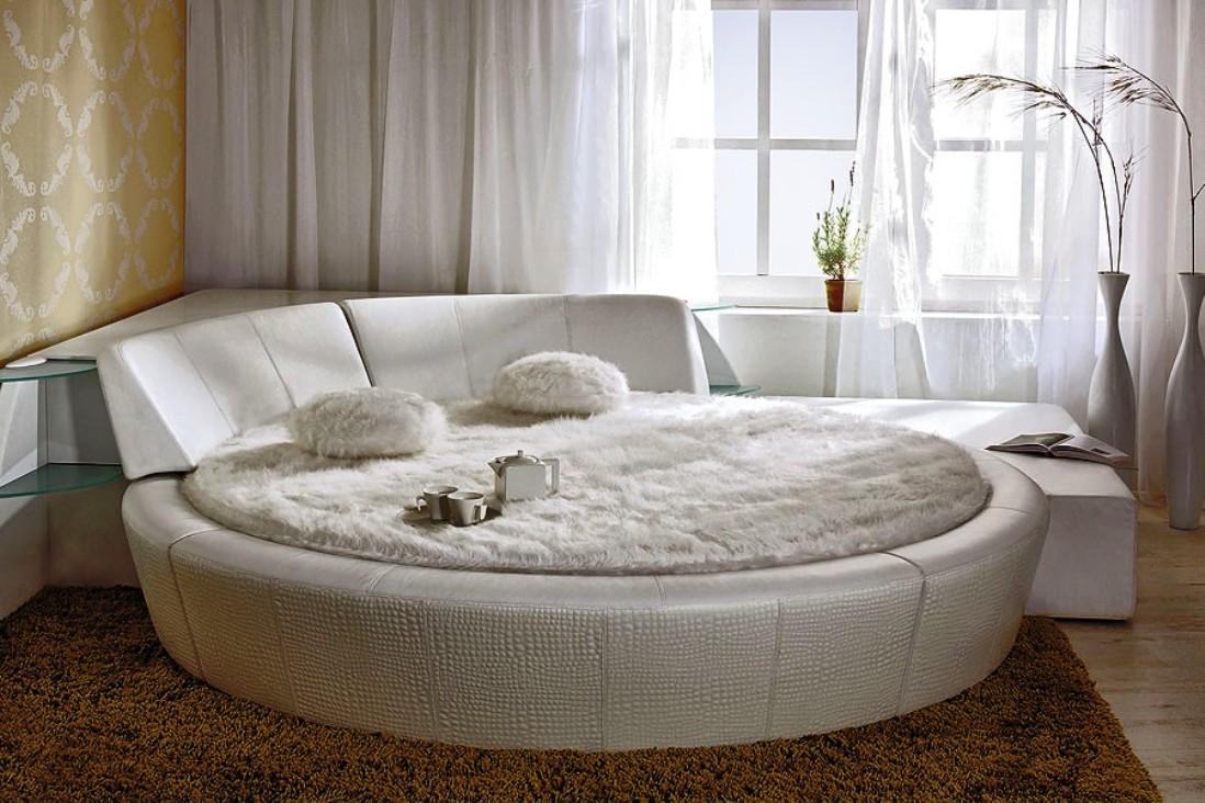 Белая круглая кровать с полками в спальне
