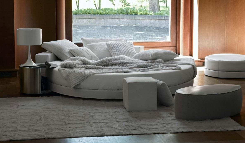 Серая круглая кровать и пуфы