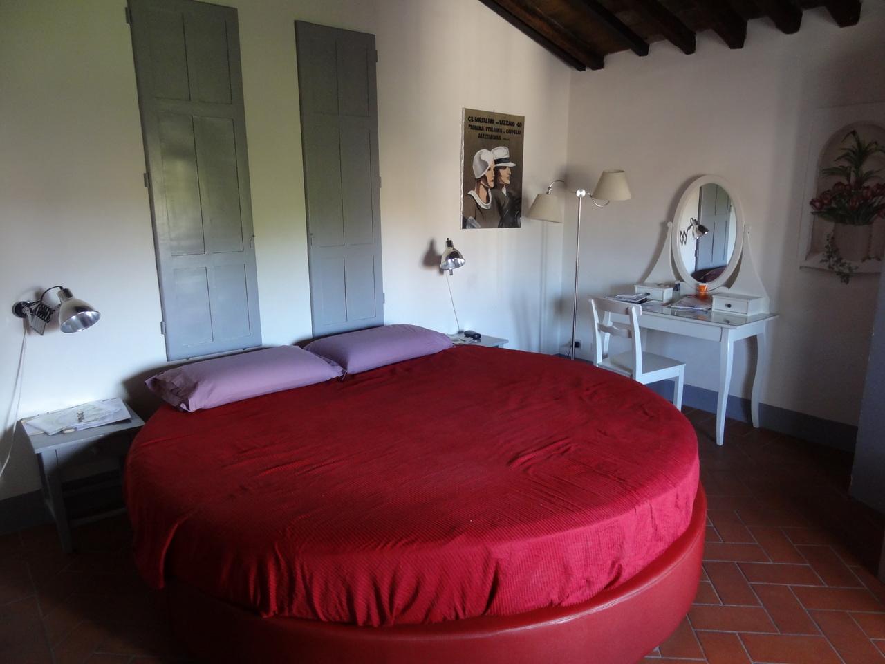 Красная круглая кровать с сиреневыми подушками