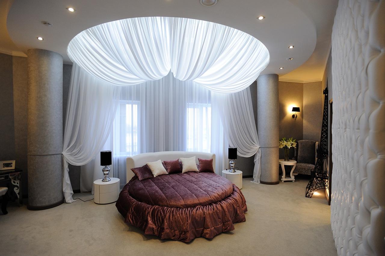 Бордово-белая круглая кровать в спальне с тканевым декором