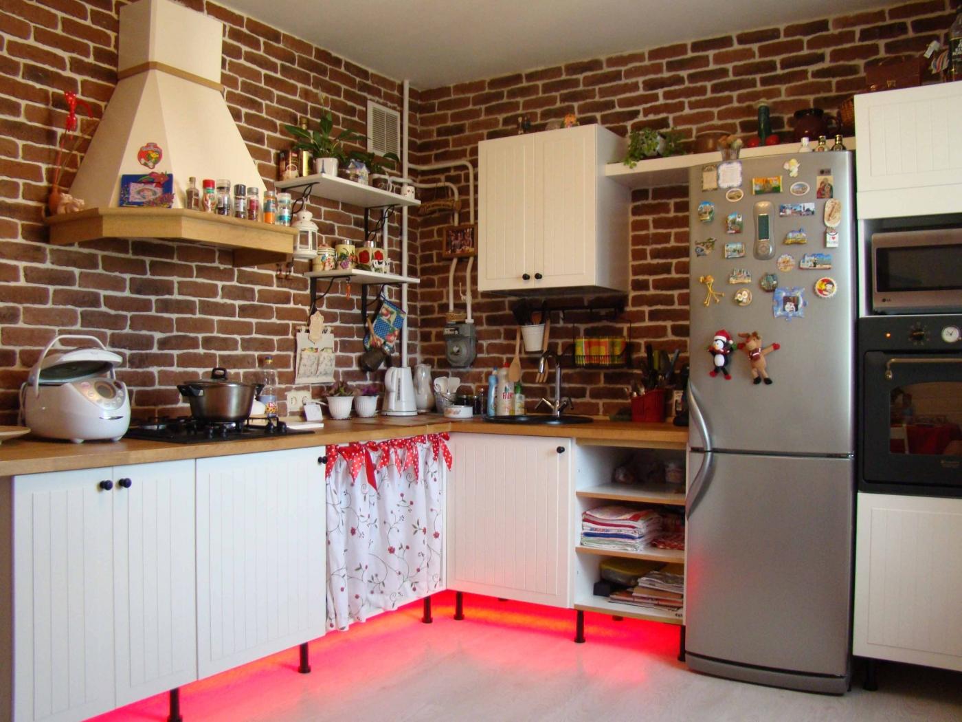 Кирпичные стены и бело-коричневый гарнитур на кухне в стиле кантри
