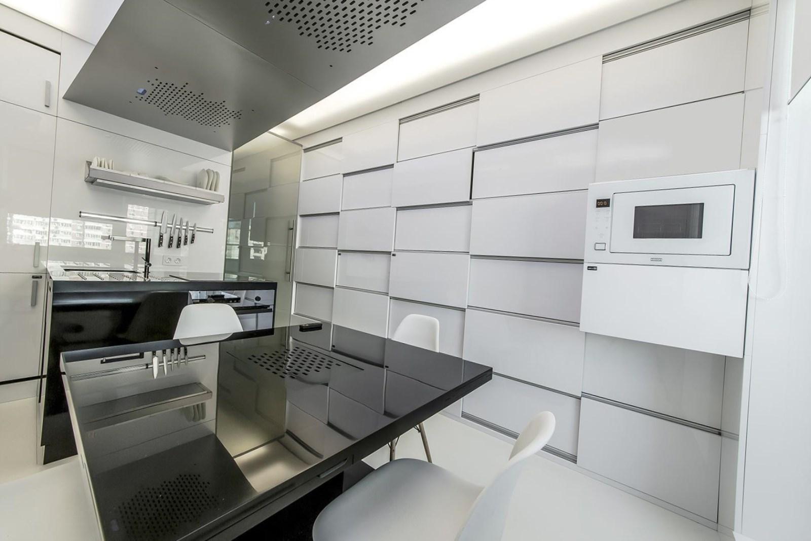 Белые стены, пол и потолок в черно-белой кухне
