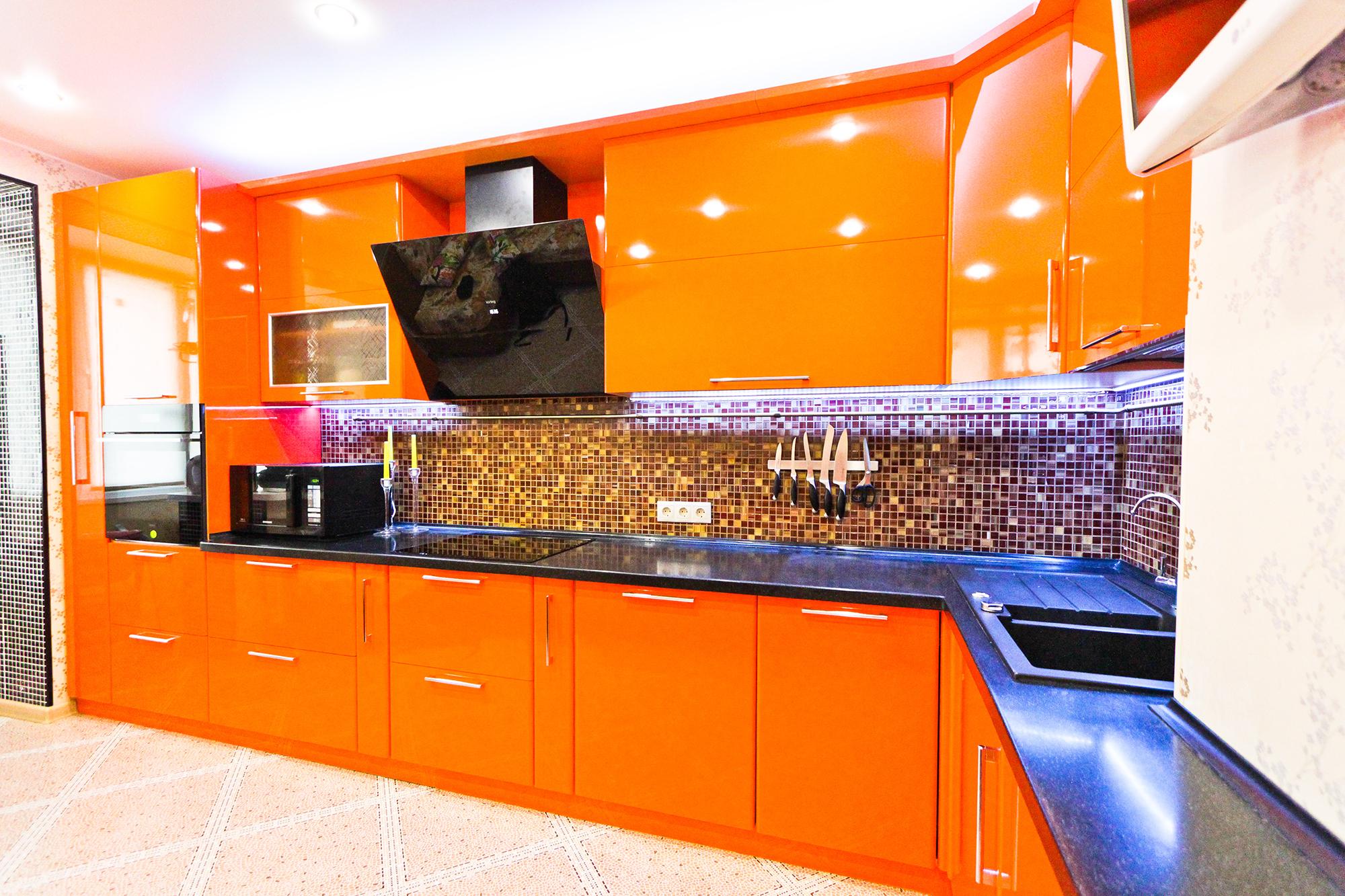 Глянцевый черно-оранжевый гарнитур на кухне