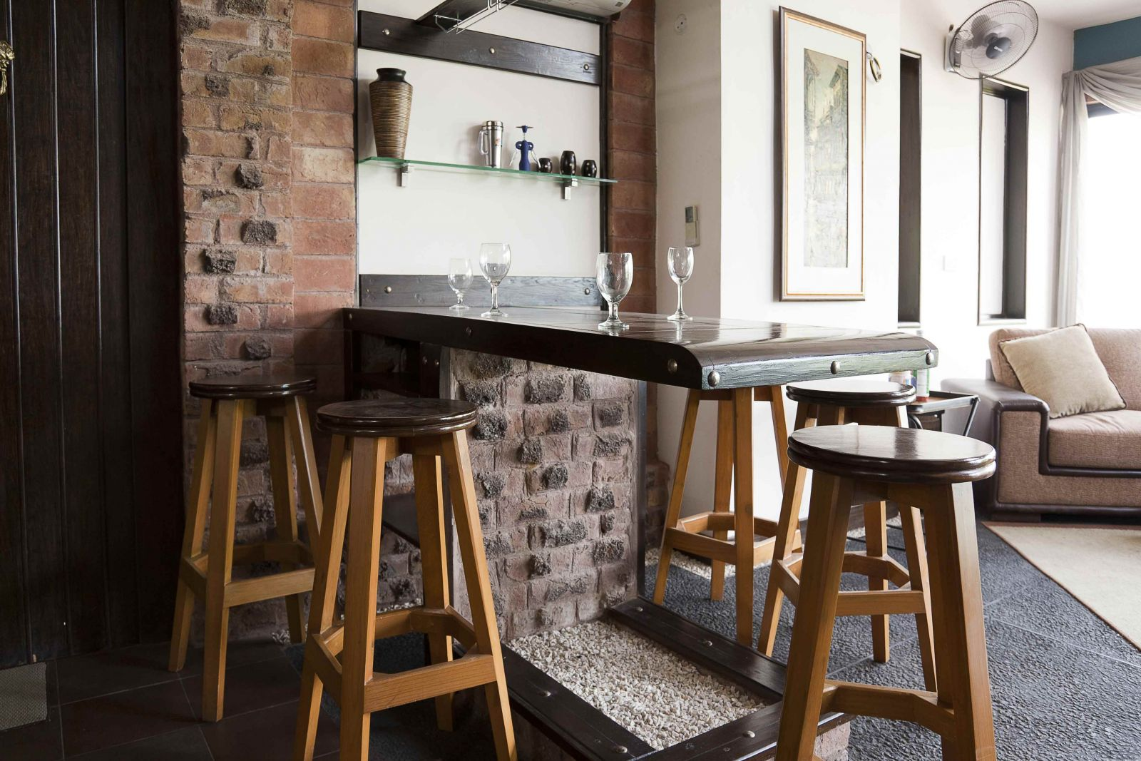 Белая и кирпичная стены в интерьере гостиной-кухни в стиле лофт