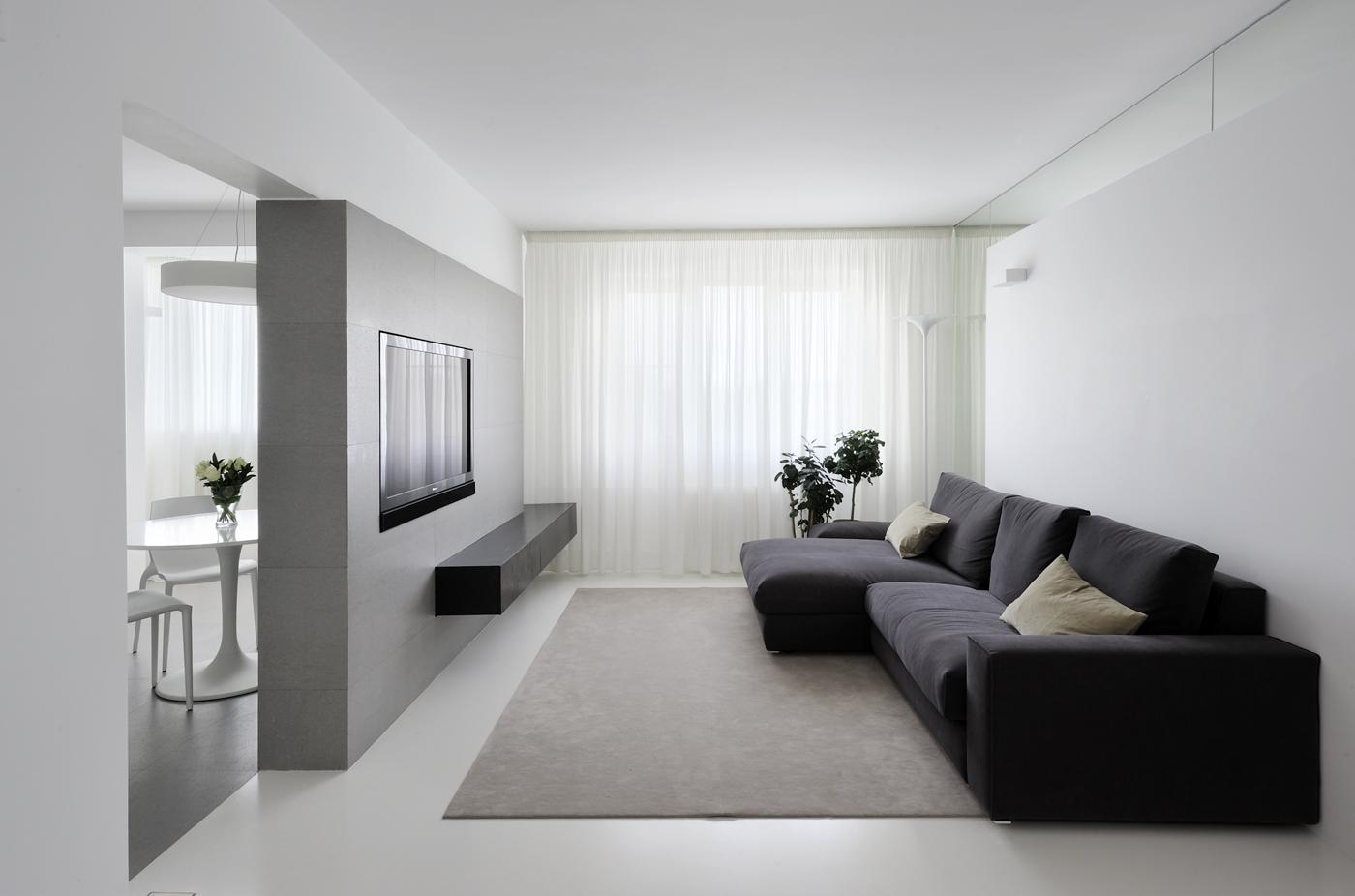 Черный диван в белой гостиной в стиле минимализм