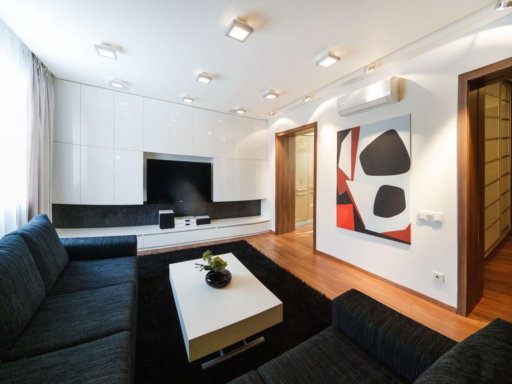 Черный угловой диван и белая стенка в стиле минимализм