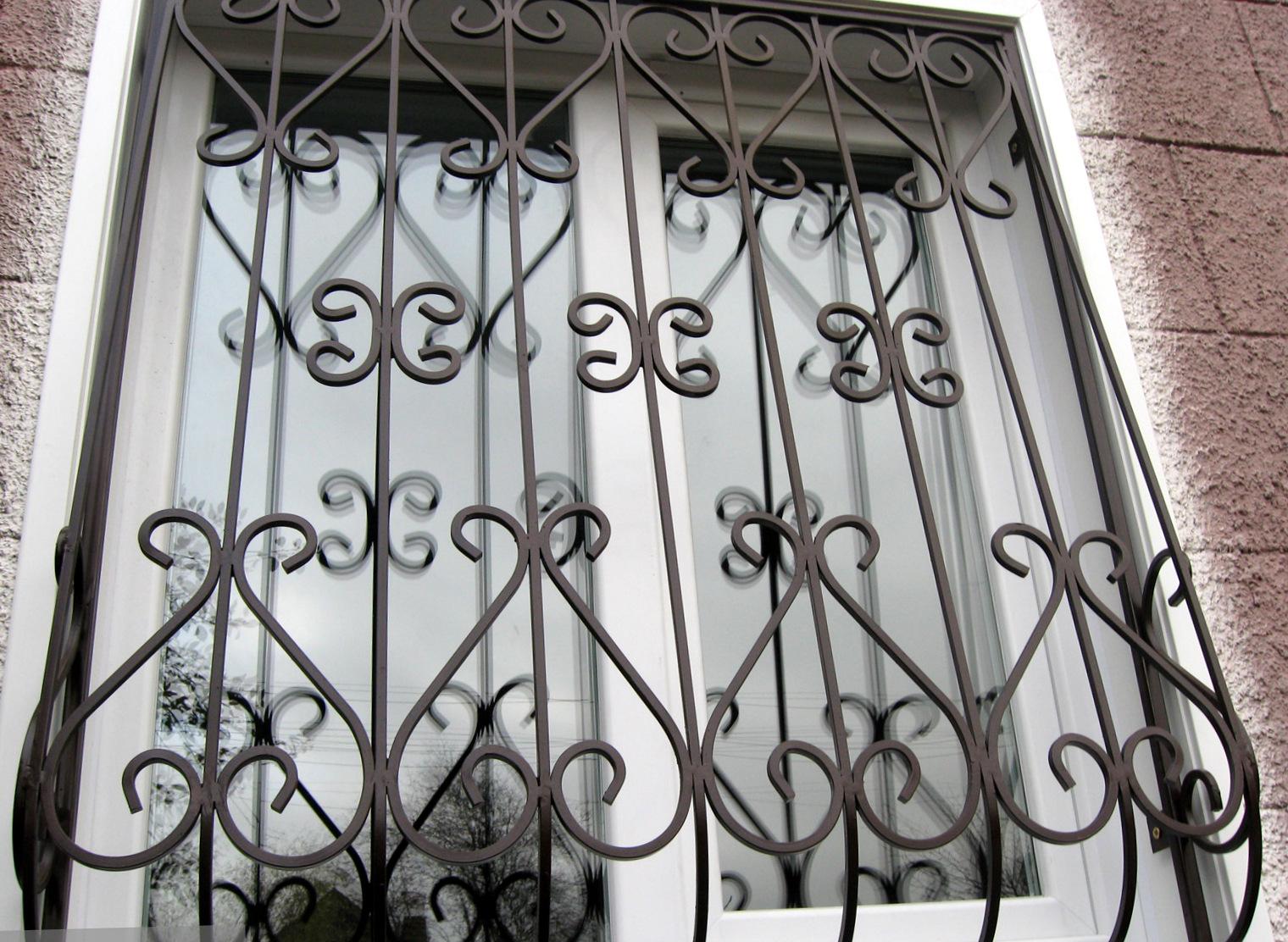 Темная решетка на окно с коваными элементами