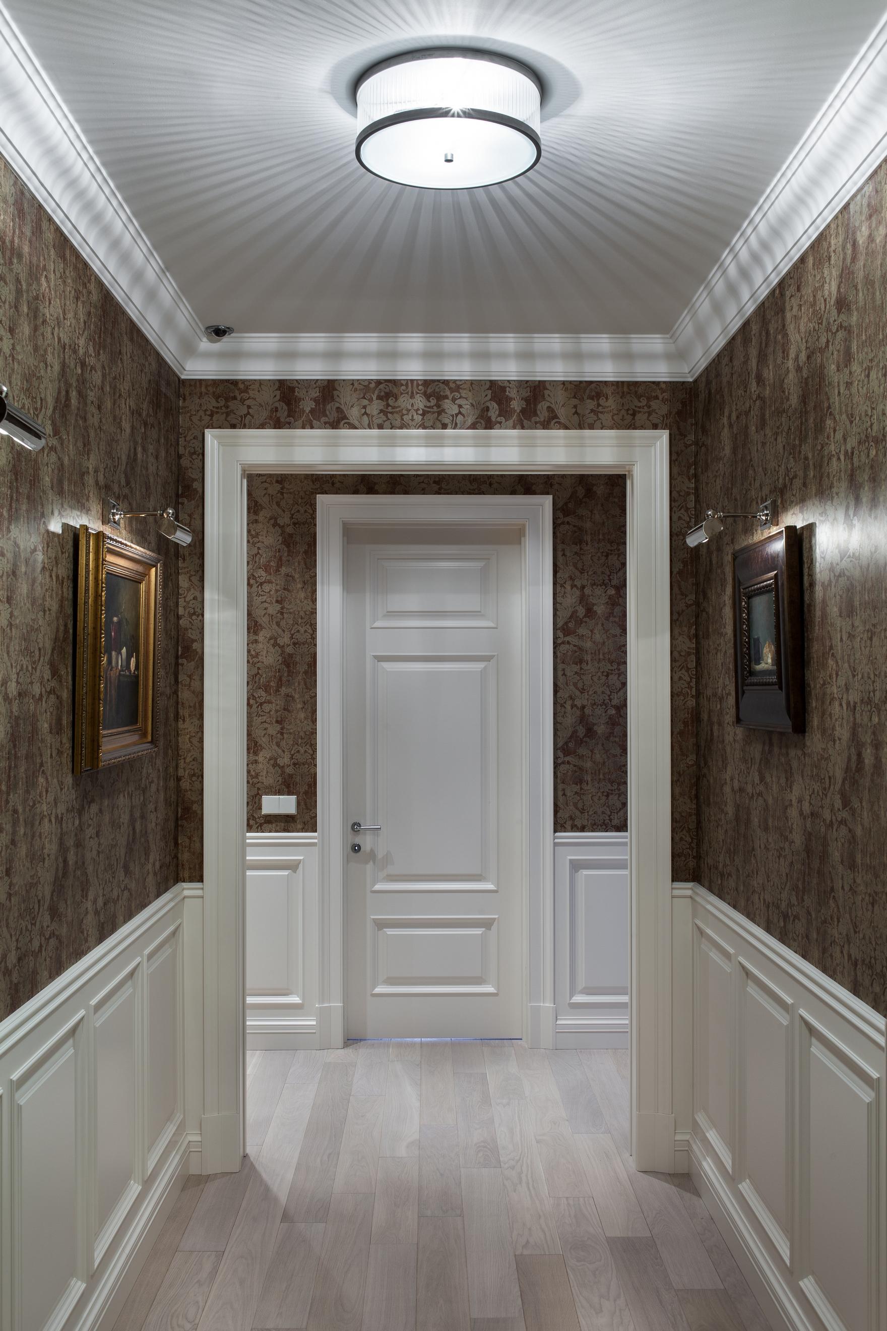 Яркая люстра и настенные светильники в коридоре