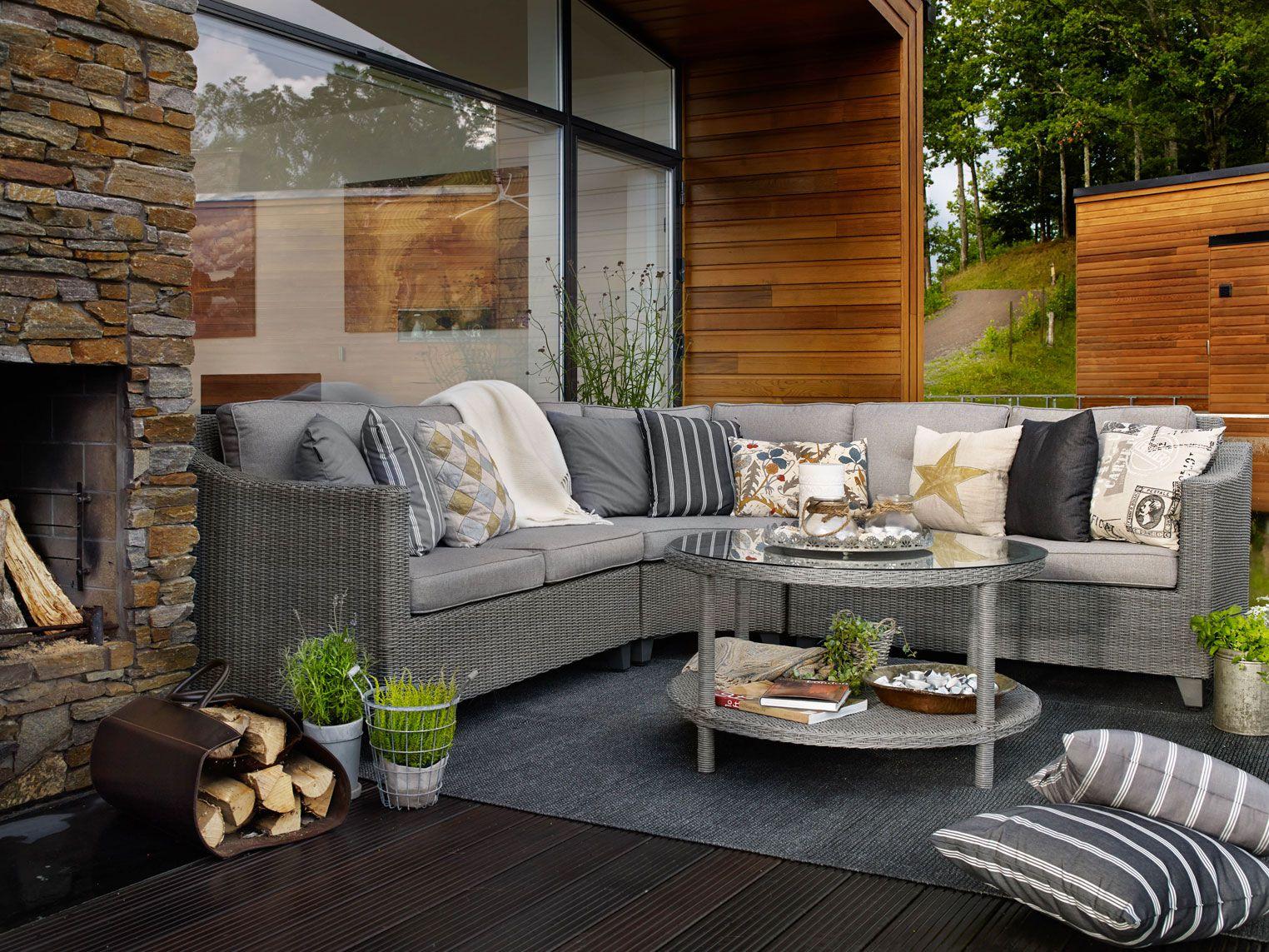 Серый плетеный угловой диван на террасе