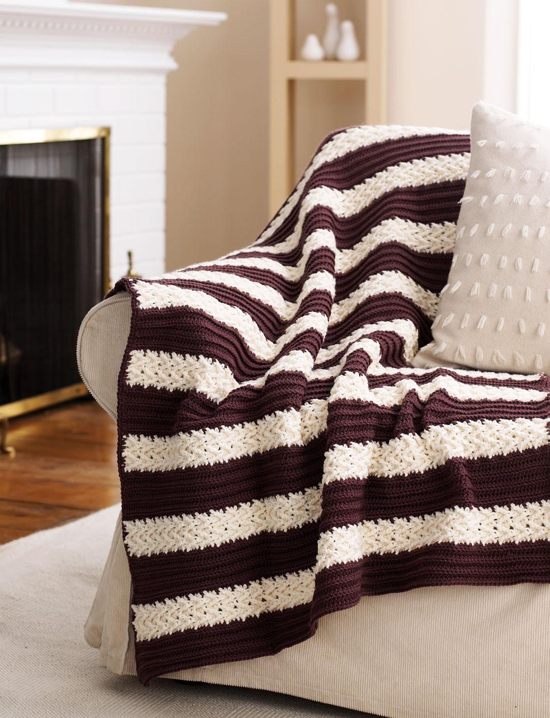 Коричнево-белое вязаное покрывало в спальне