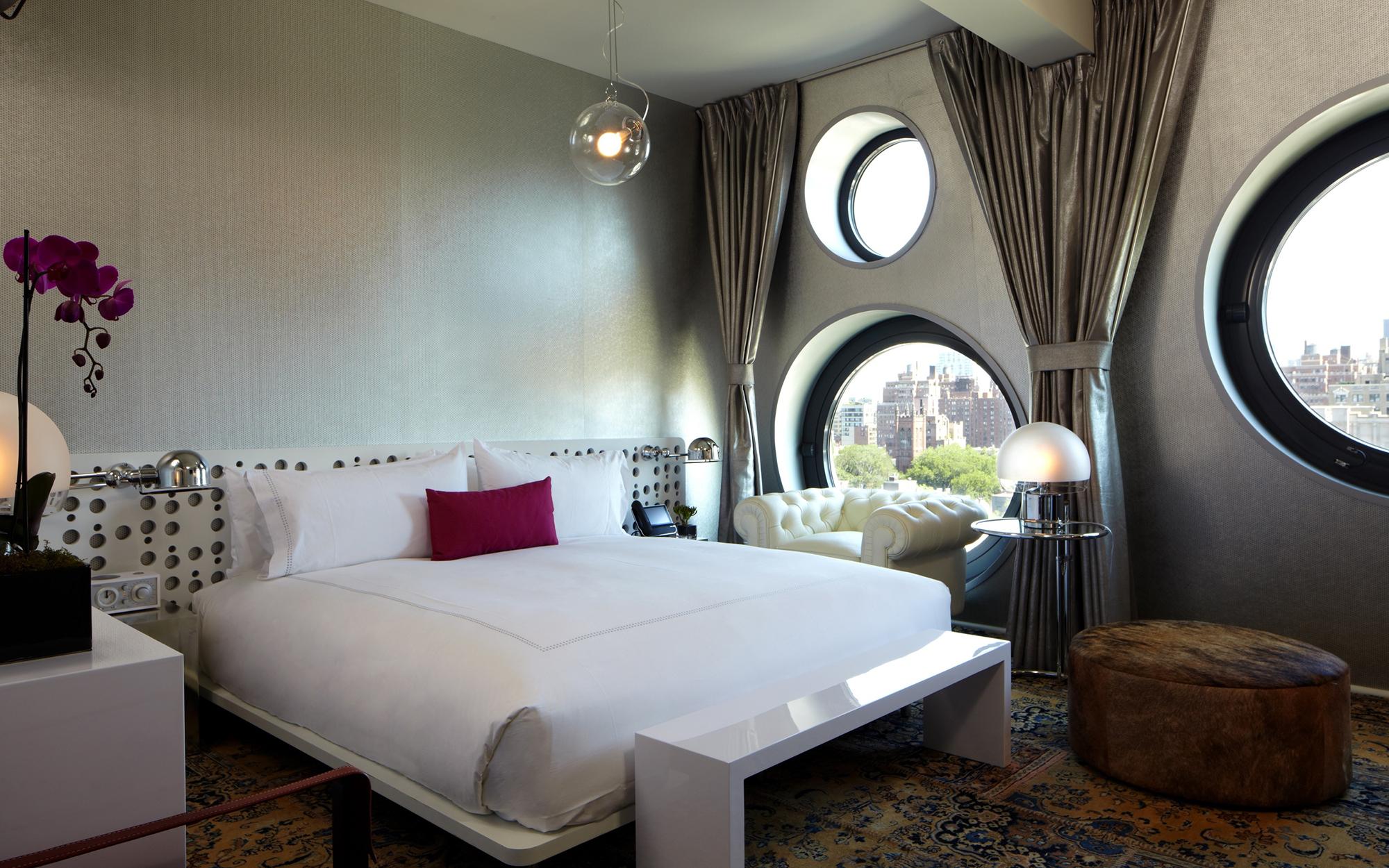 Серо-белая спальня с круглыми окнами