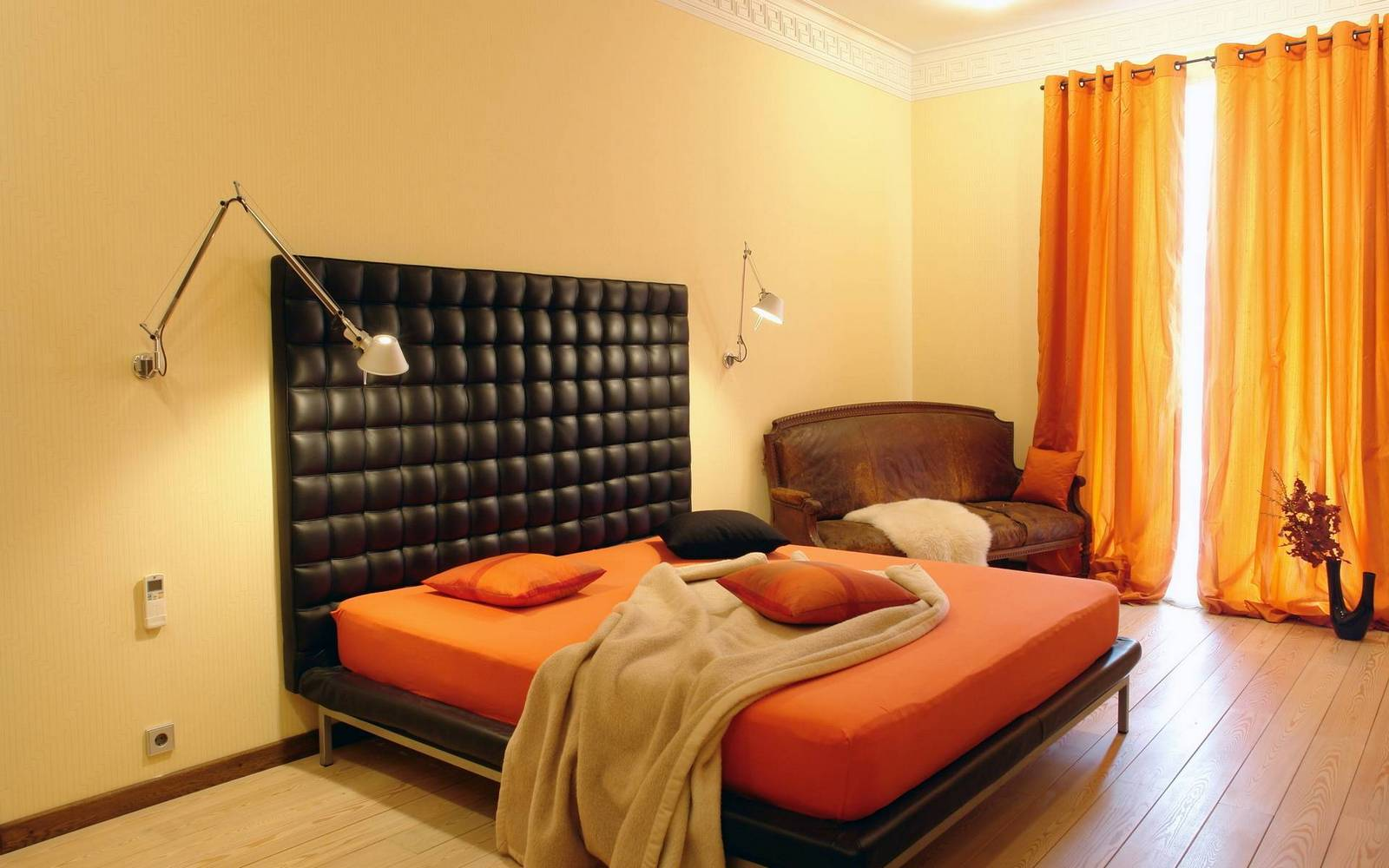 Кремово-оранжевая спальня с черной кроватью
