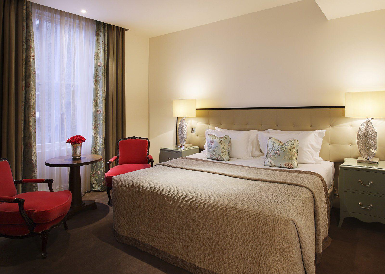 Бежево-белая спальня с красными и зелеными акцентами